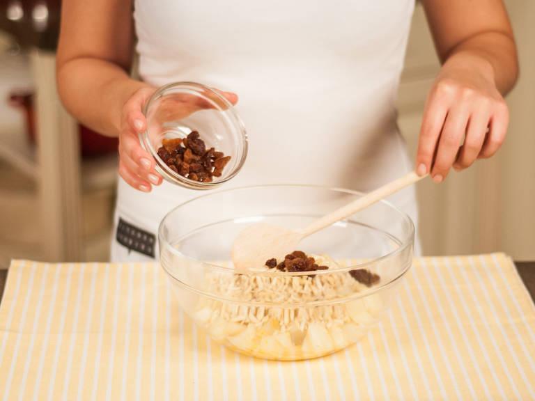 将梨、杏仁片、白兰地酒、刮出的香草精华和无籽葡萄干放入碗中,拌匀。将混合物倒在挞底上。
