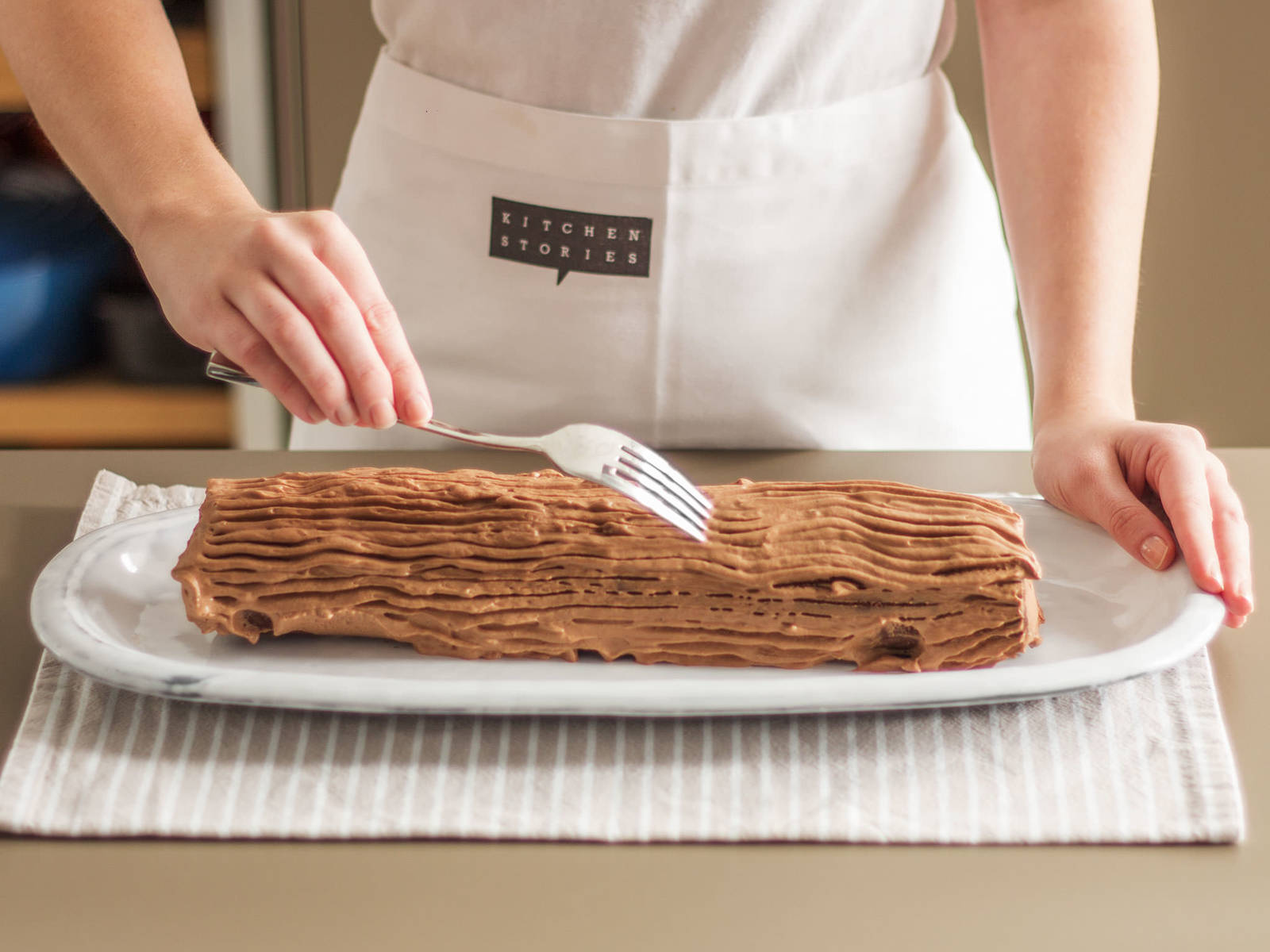 Distribute two thirds of the cream over the cake and roll it up. Place on a long serving plate and decorate with remaining cream. It is traditional to pull the tines of a fork over the cream to make it look like tree bark. Bon appétit!