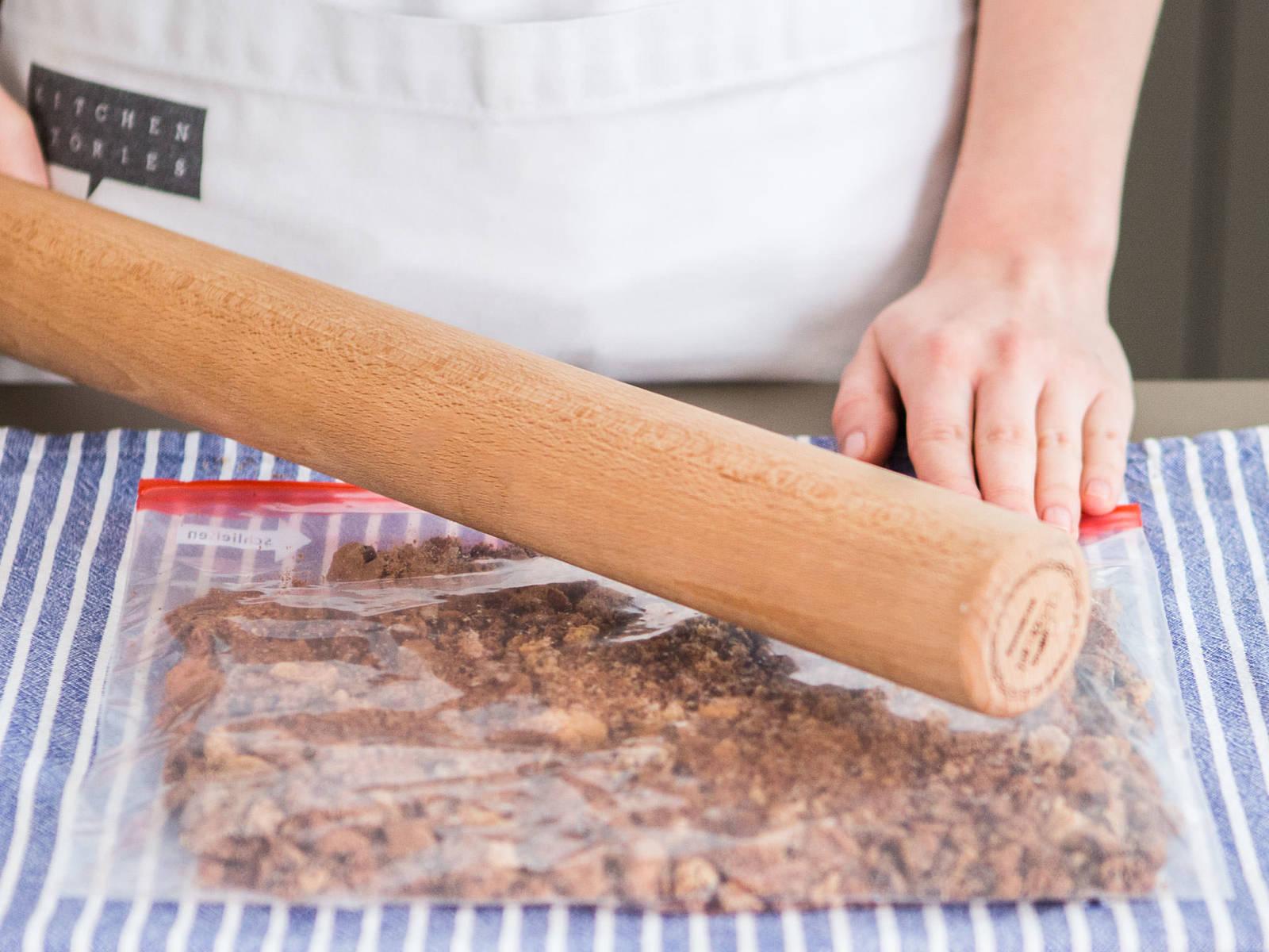 Cookies in einem Gefrierbeutel geben. Beutel gut verschließen und Cookies anschließend mit einem Nudelholz zerbröseln.