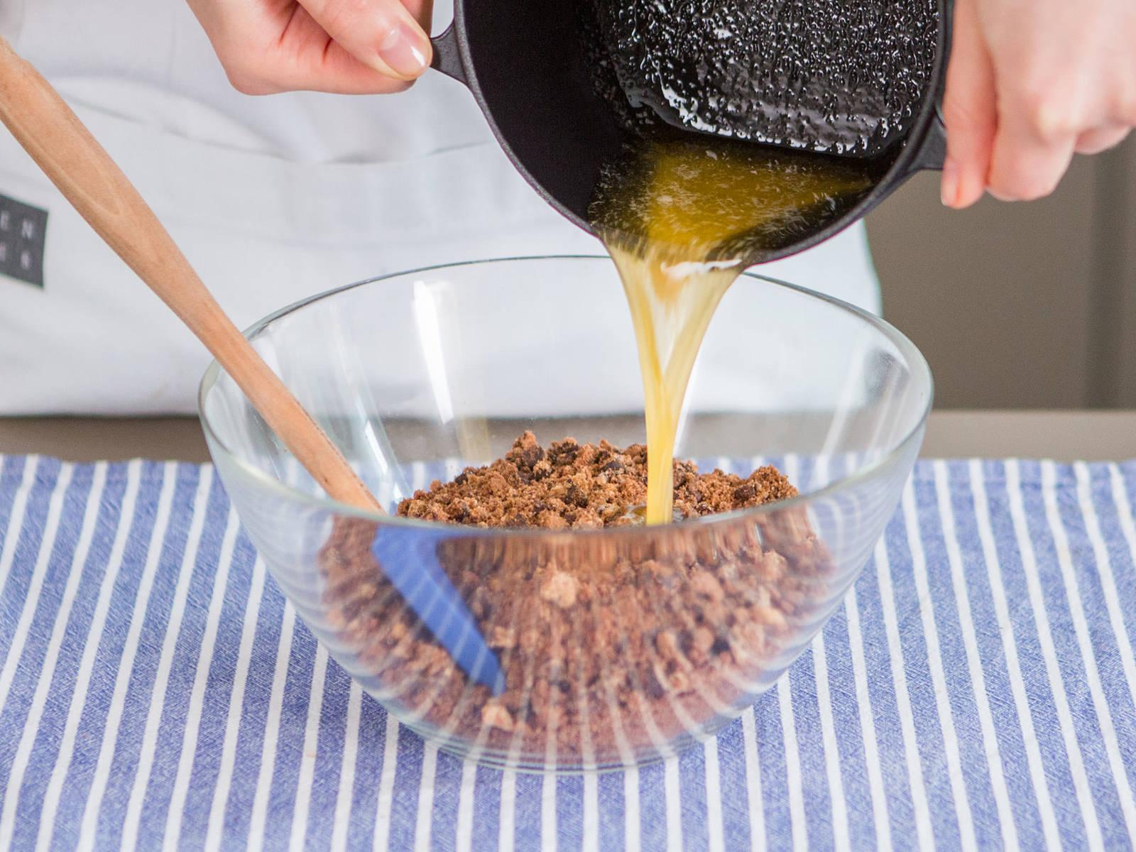 用中温在小锅中融化黄油。将饼干碎放入大碗,将融化后的黄油倒在其上,搅拌均匀。