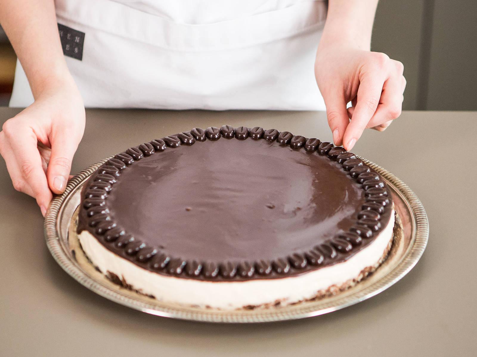 用刀沿烤模内侧轻轻转一圈,将蛋糕放入蛋糕盘。将巧克力混合物均匀涂抹在奶酪蛋糕上,用咖啡味巧克力装饰最外圈。佐一杯冷百利酒享用!