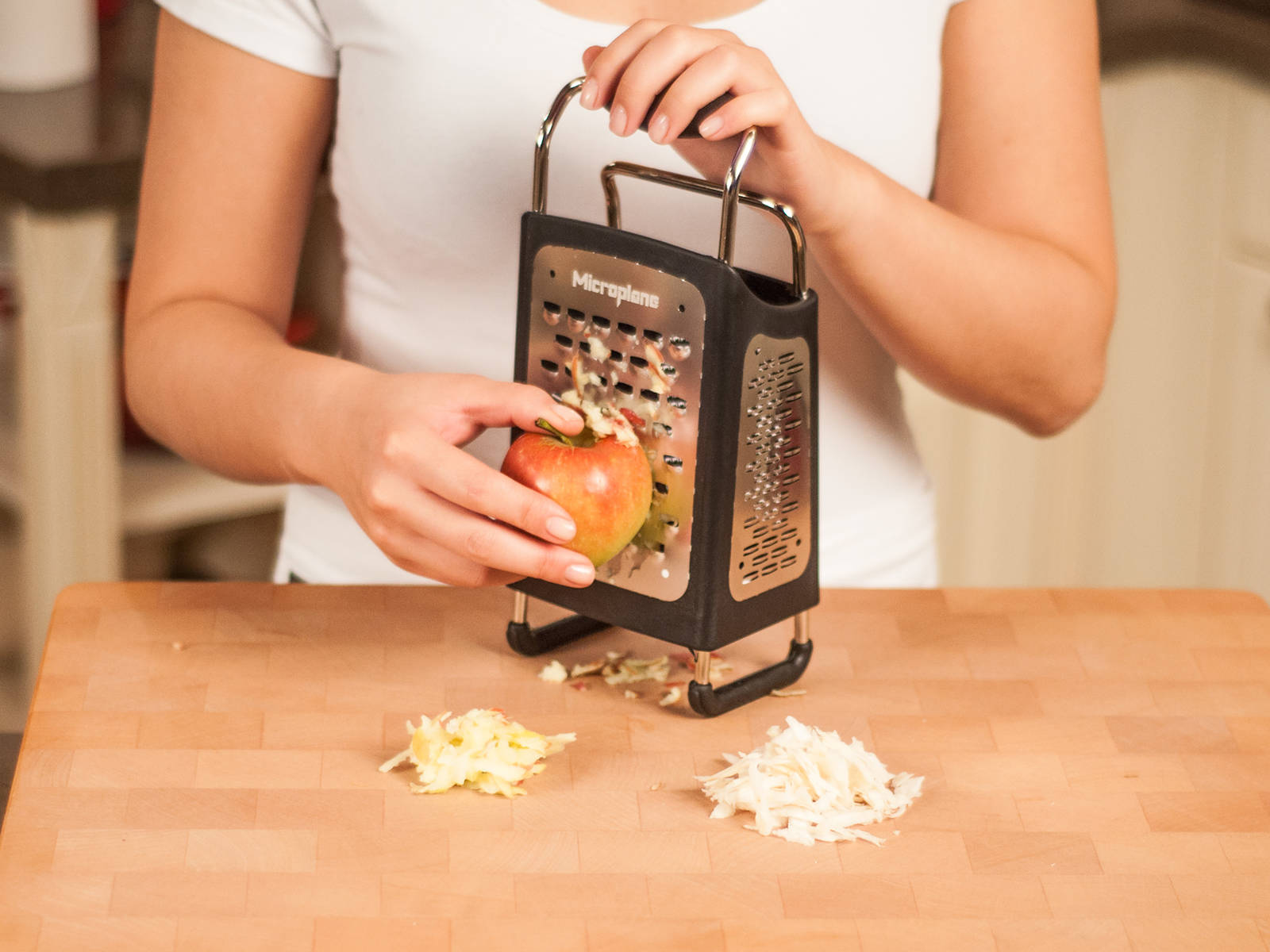 削掉根芹皮。用盒式擦菜板上的大孔面擦碎根芹和苹果。