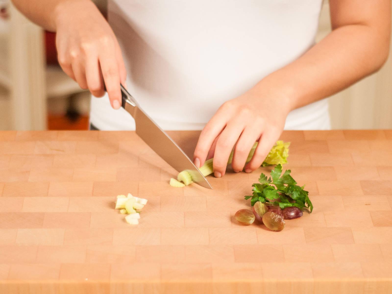 将欧芹粗粗剁碎,葡萄切成两半,芹菜茎切成薄片。