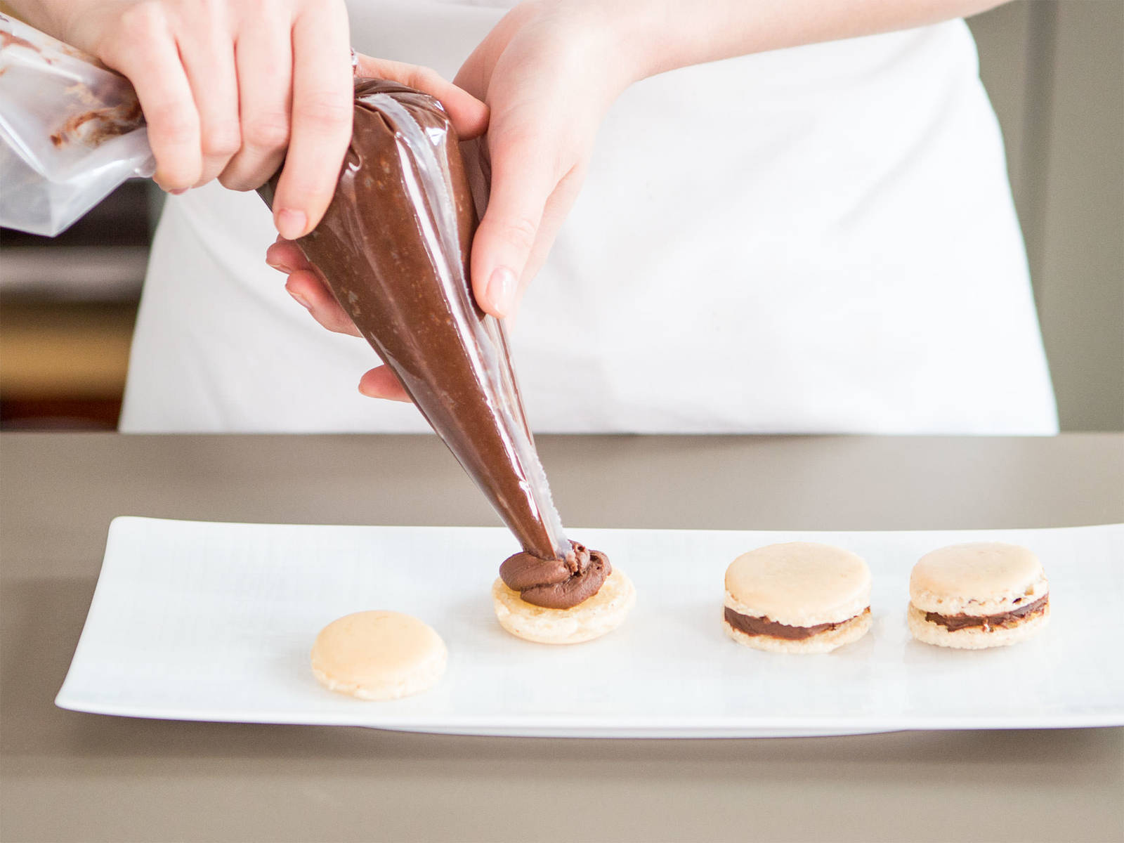 Pipe coffee buttercream onto the bottom half of a macaron. Place another half on top and lightly press. Repeat until macarons are assembled. Enjoy with a cup of coffee!