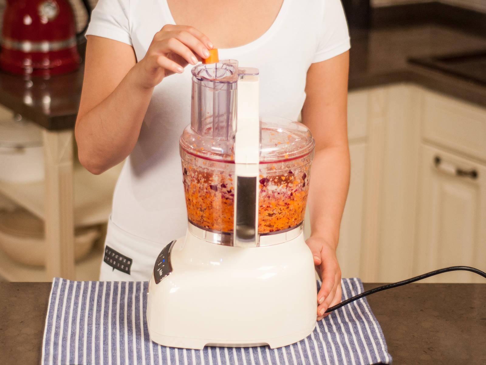 将扁豆、大蒜、小米、豌豆、洋葱和胡萝卜放入食品加工机中搅打。