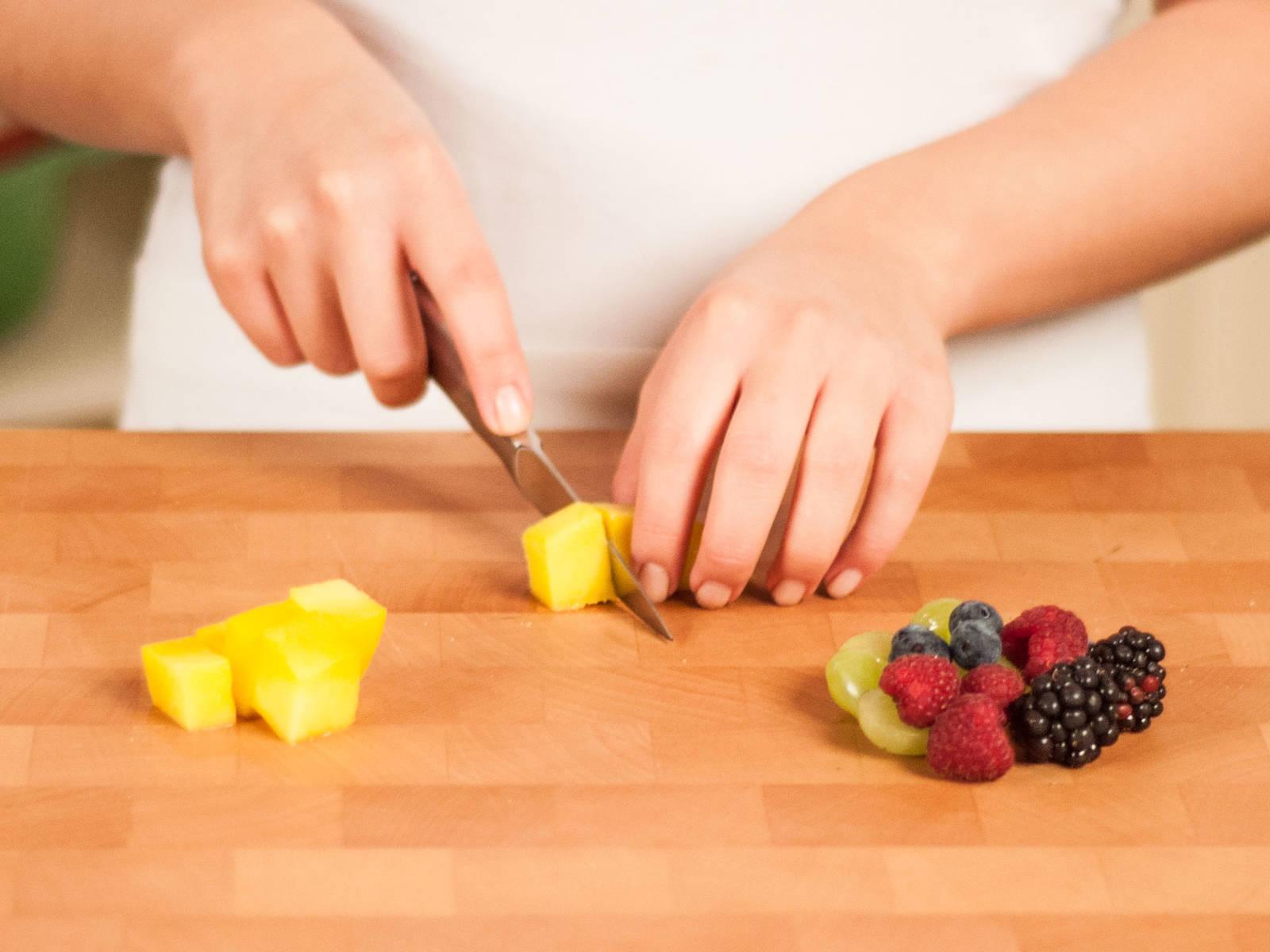 Set berries aside. Halve grapes. Peel mango and cut into cubes.