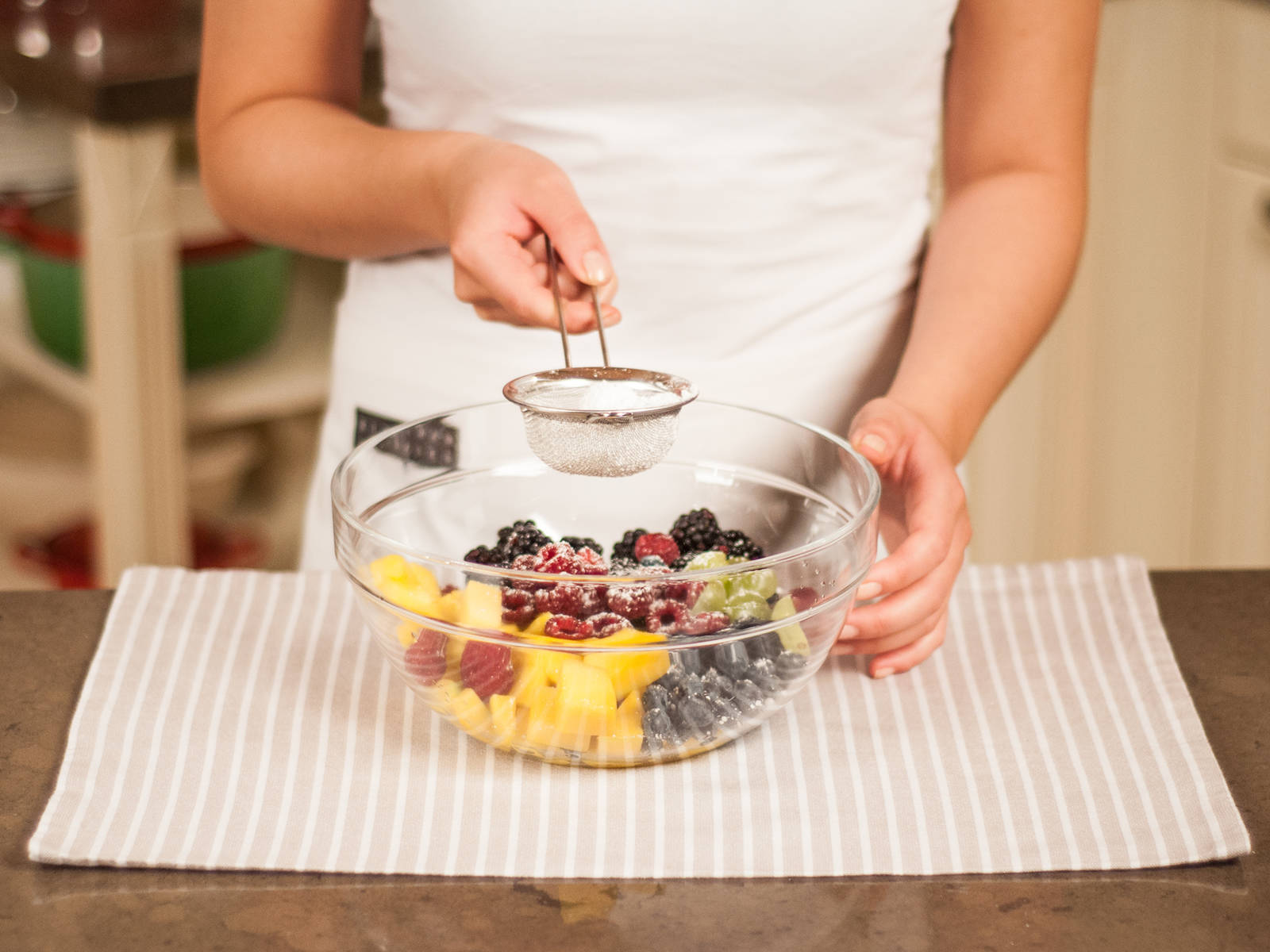 Transfer all fruit to a large bowl. Juice lemon and add to fruit salad, as well as sifted confectioner's sugar. Mix well.