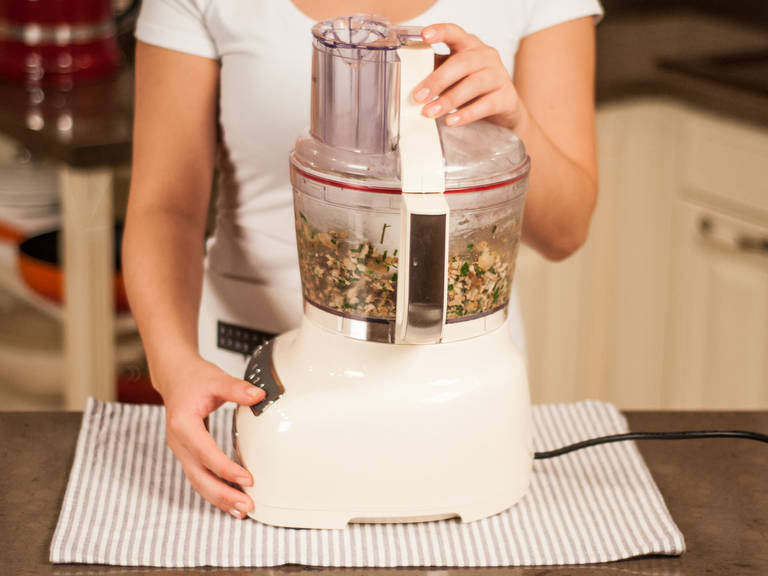 将煮熟的兵豆与煸炒好的蔬菜加入食品加工机中,加入欧芹、布丁、鸡蛋与燕麦,大致搅碎。
