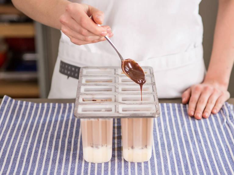 粗略切碎巧克力。用低温在小锅中加热剩余奶油,加入巧克力,搅拌至融化。将融化后的巧克力加入每个冰棒模具中。加盖后插入冰棒棍,放入冰箱冷冻4-6小时。