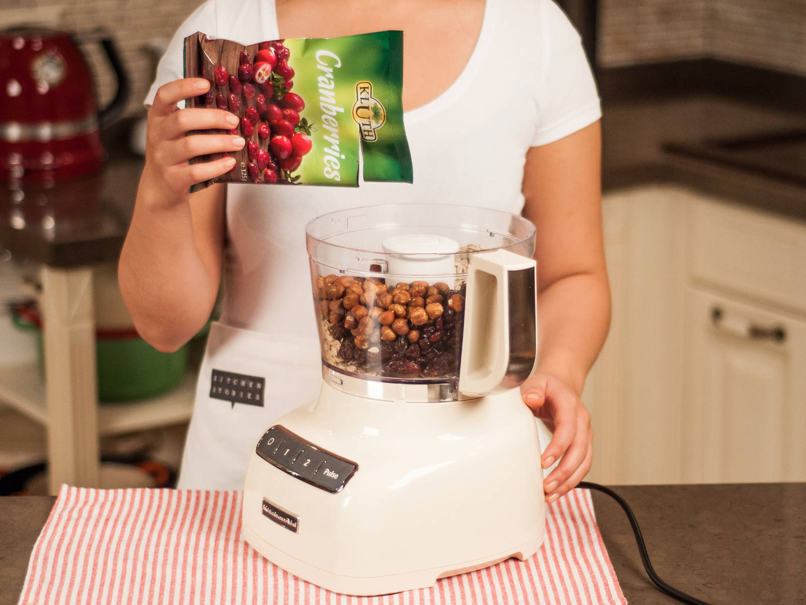 Add oatmeal, hazelnuts, sunflower seeds, dates, apricots, and cranberries to a food processor.