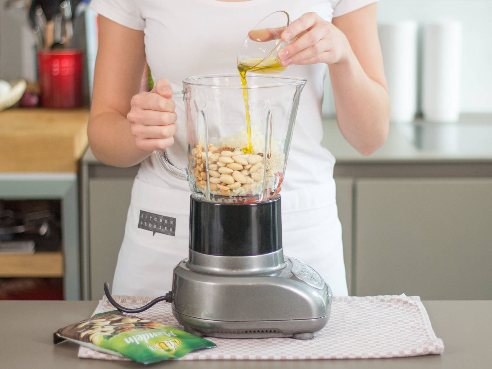Add onions, tomatoes, chilis, peanuts, almonds, clove, cinnamon, sesame seeds, and olive oil to a blender. Blend for approx. 2 – 3 min. into a smooth pesto.