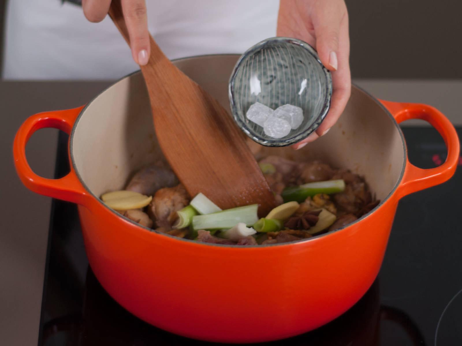 向锅中加入葱段、姜片、八角与冰糖。