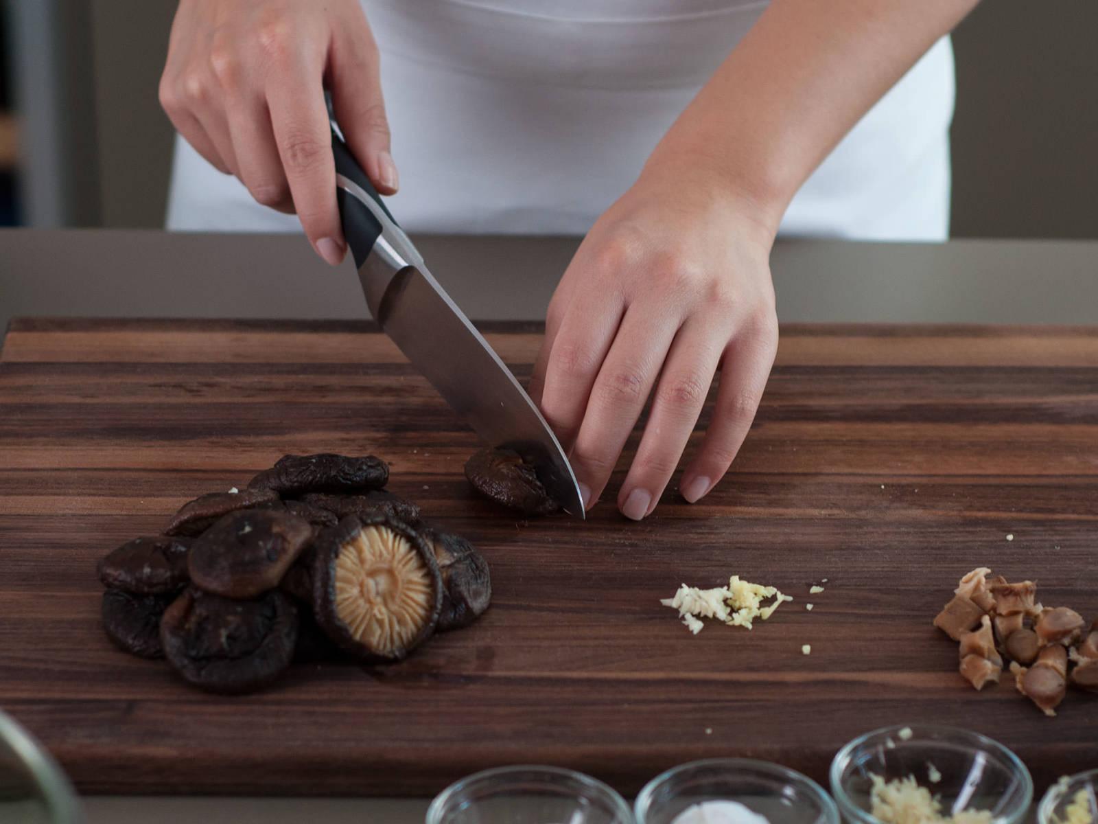 将干香菇在热水里泡大约20分钟,直至香菇头变软。浸过香菇的水备用。剁碎蒜和姜。切掉香菇根,在香菇头上划一个十字。