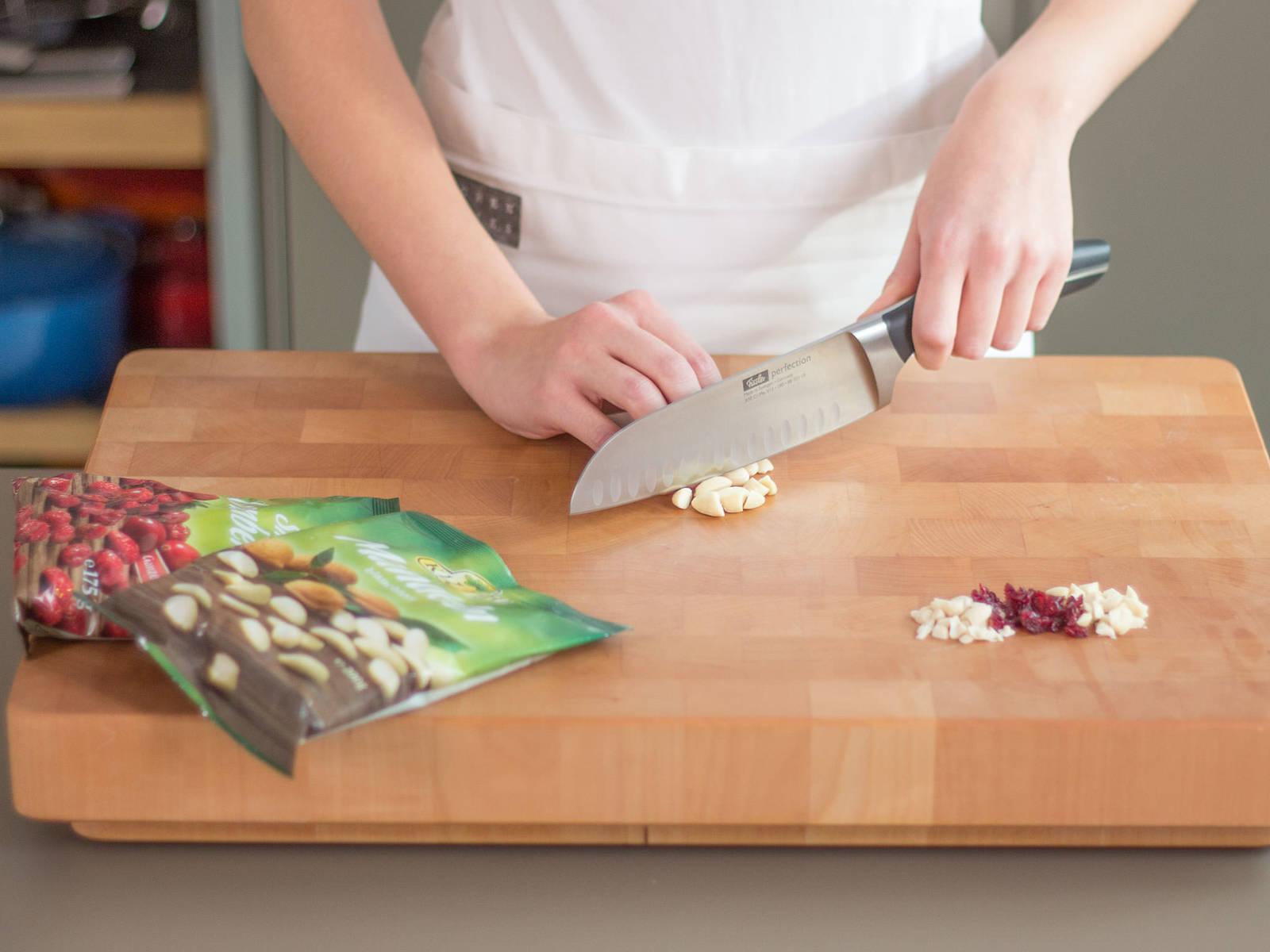 将烤箱预热至180度。大略切碎蔓越橘干、杏仁和花生。