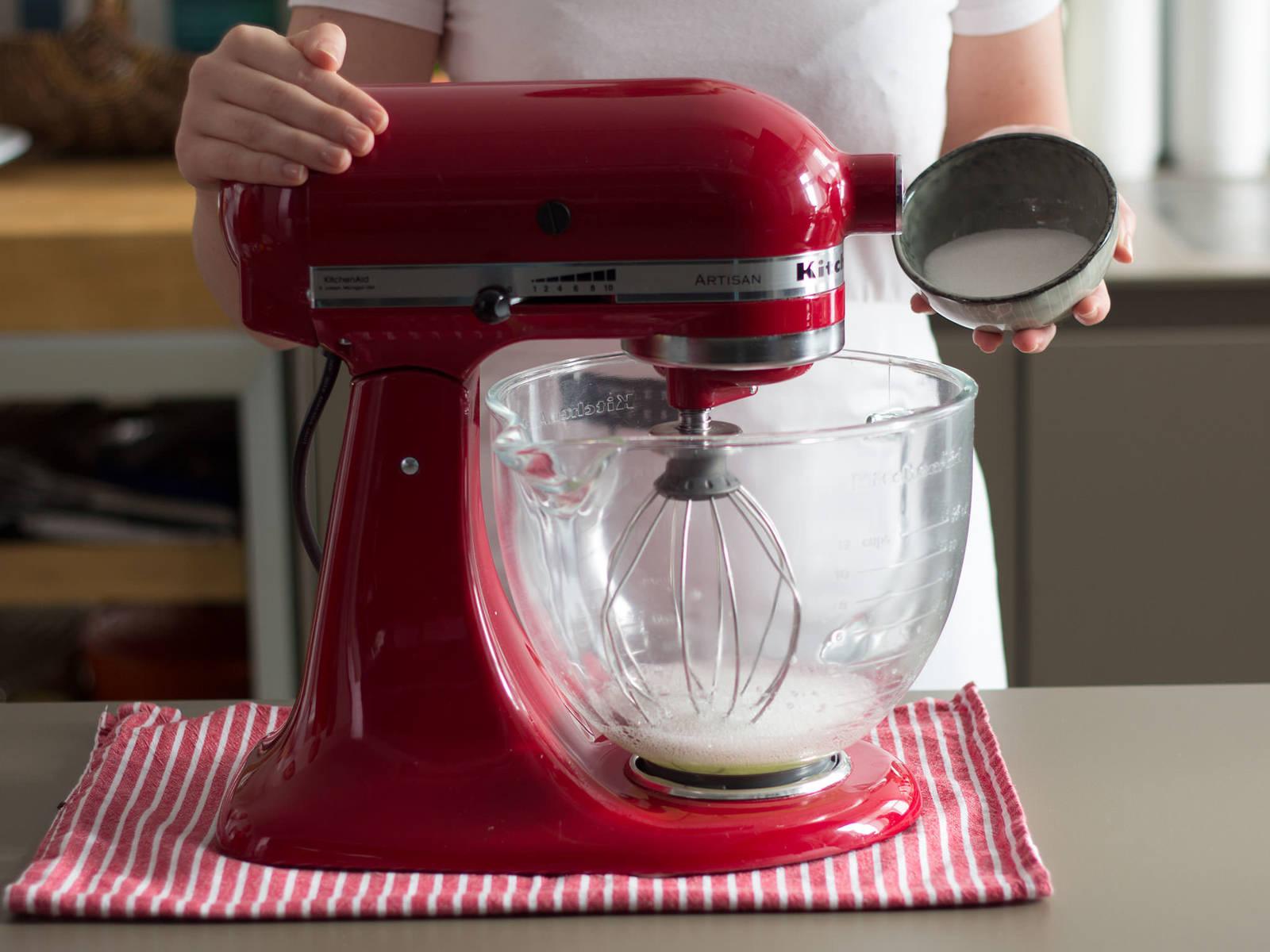 Eiweiß und einen Teil des Zuckers in eine saubere Schüssel geben und in der Küchenmaschine aufschlagen, bis sich steife weiße Spitzen formen.