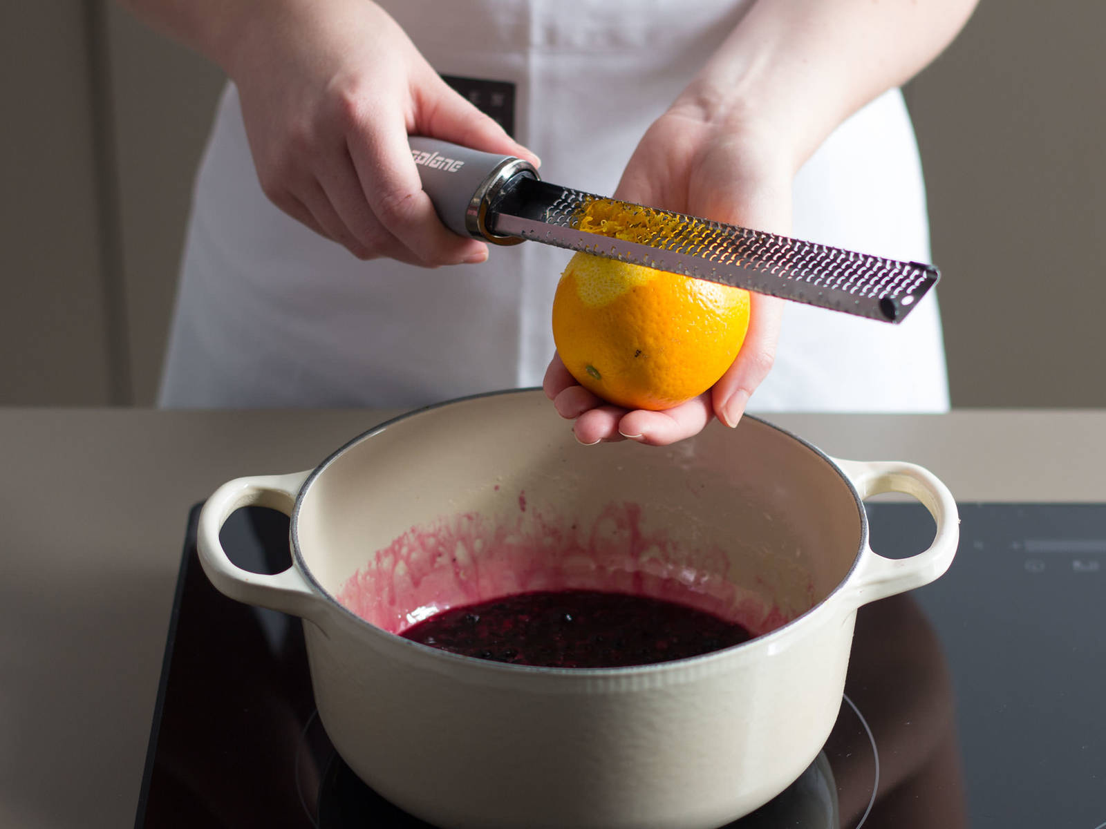 For the blueberry sauce, caramelize remainder of sugar in a large saucepan over medium-low heat for approx. 3 – 5 min., stirring constantly. Deglaze with lemon and orange juice. Then, add frozen blueberries, remainder of vanilla pod, and zest from lemon and orange and continue to cook for approx. 5 – 7 min. until sauce thickens.