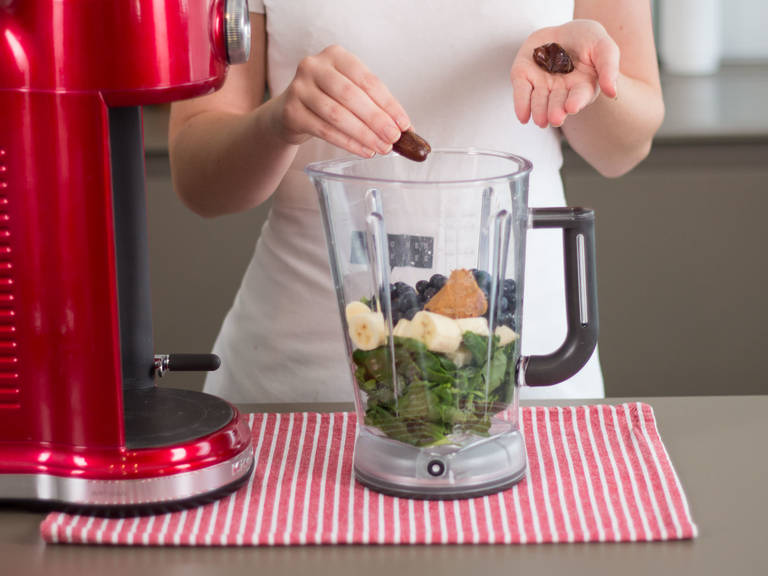 Add spinach, banana chunks, blueberries, peanut butter, ice cubes, and dates to blender.
