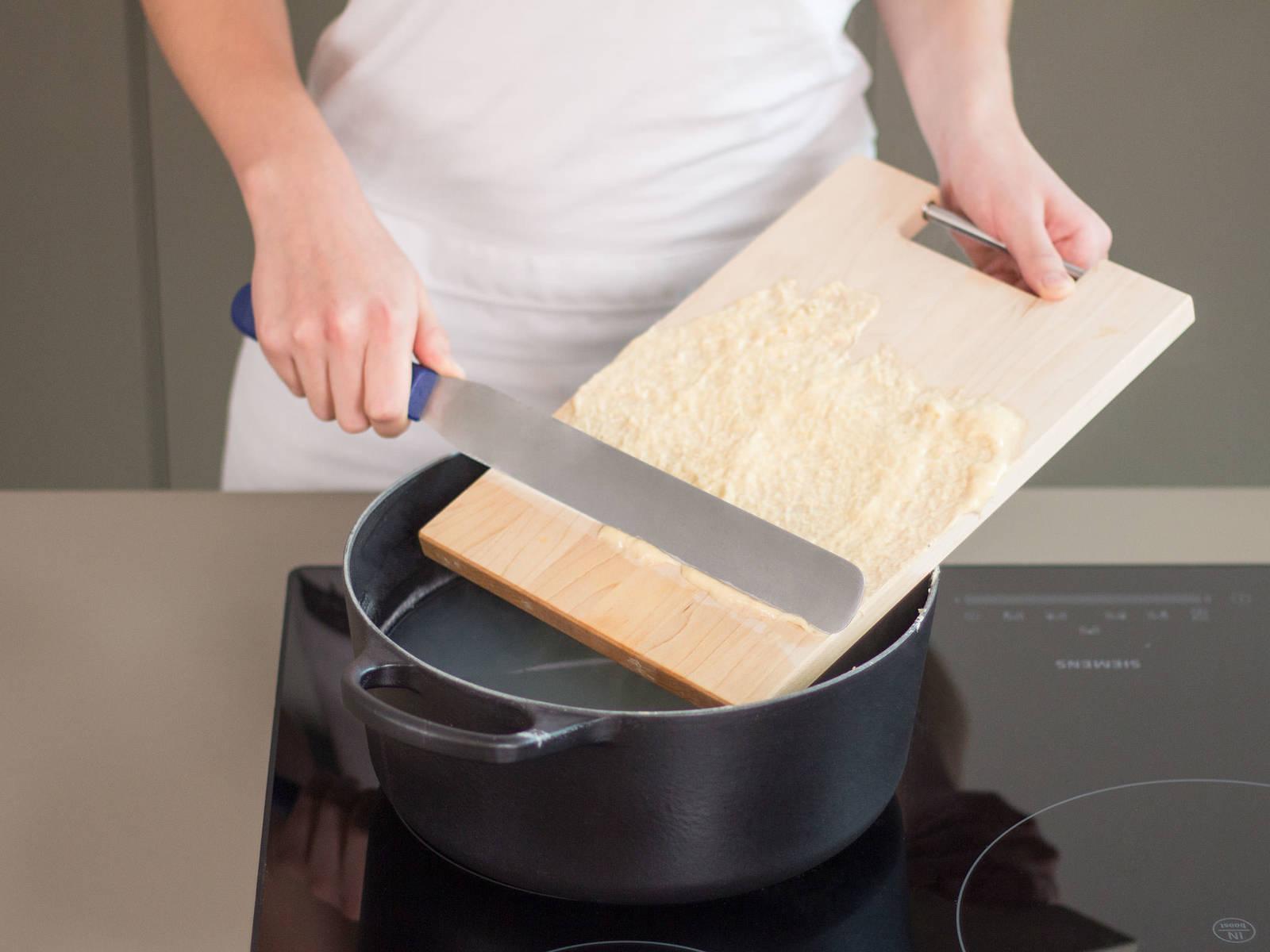 Einen großen Topf zur Hälfte mit gesalzenem Wasser füllen und bei mittlerer Hitze zum Kochen bringen. Schneidebrett mit ein wenig kochendem Wasser benetzen und anschließend mit einer dünnen, ebenmäßigen Schicht Teig bestreichen. Mit einer Kuchenpalette dünne, etwa stiftdicke Streifen Teig vom Brett in den Topf schaben. Ca. 1 Min. kochen, bis die Spätzle an die Wasseroberfläche steigen. Anschließend in Eiswasser ca. 20 Sek. abschrecken. Zum Abtropfen, in ein Sieb geben.