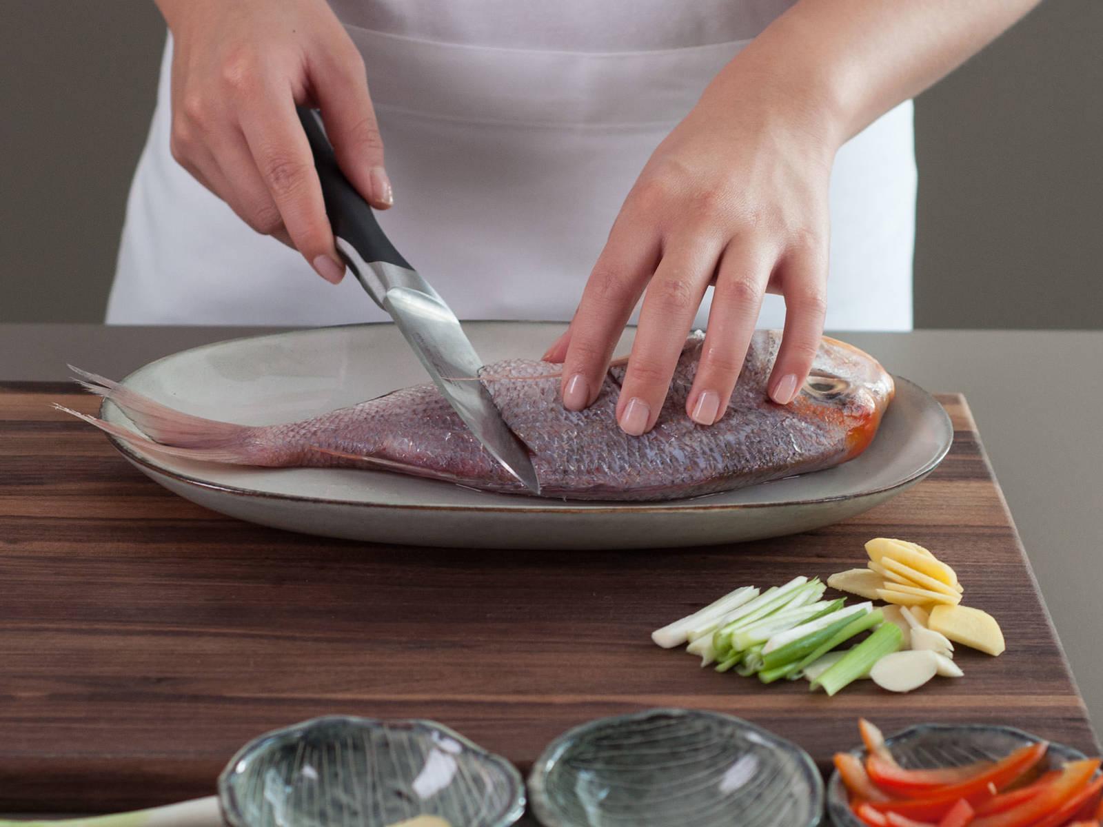 Die Hälfte des Ingwers und den Knoblauch in dünne Scheiben schneiden. Paprika in Julienne schneiden. Die Hälfte der Frühlingszwiebel in kurze Streifen schneiden. Den Fisch auf beiden Seiten diagonal einschneiden. Mit Salz bestreuen und mit Wein übergießen.