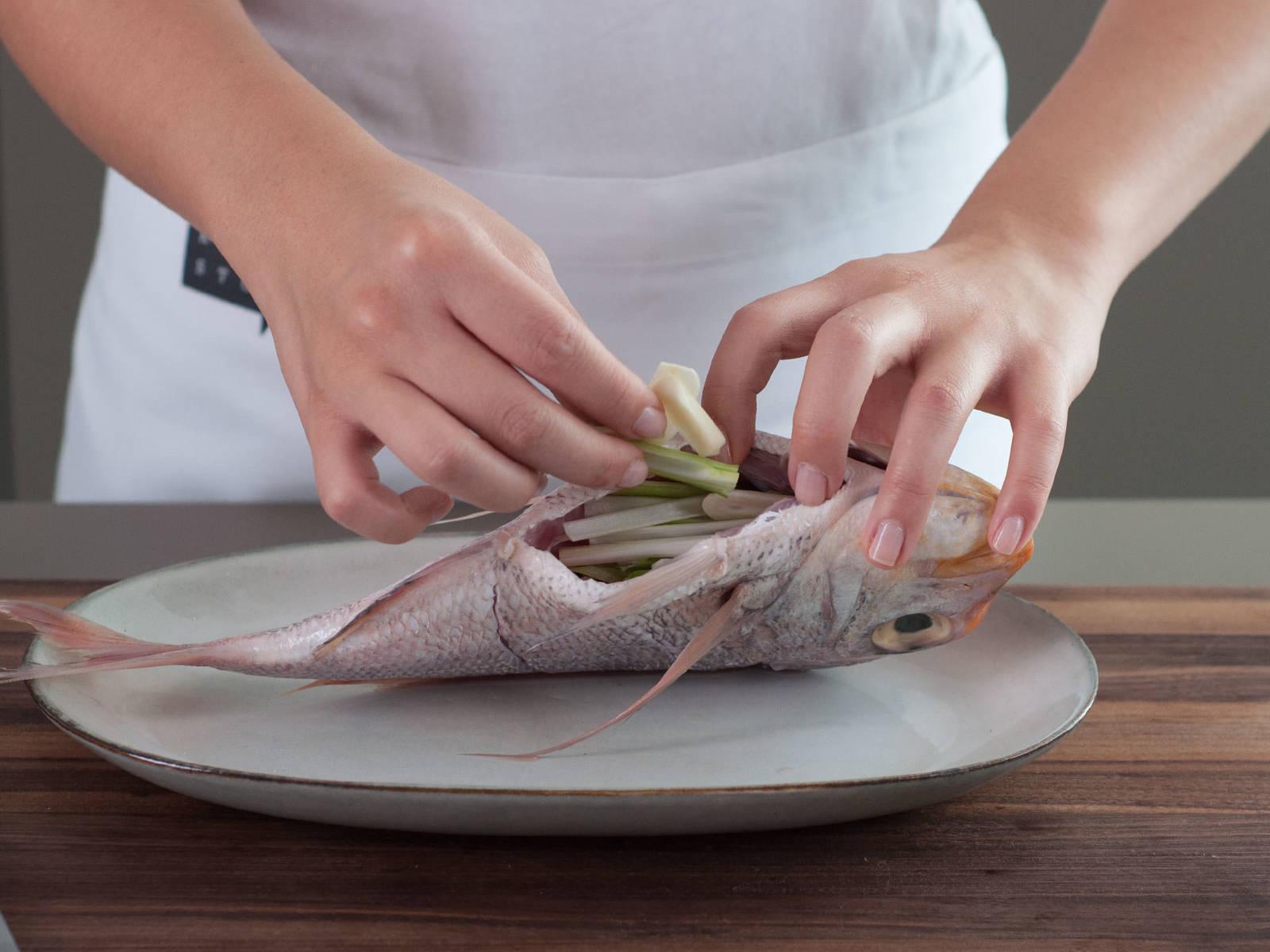 Fisch mit gehackten Frühlingszwiebeln, Ingwer und Knoblauchscheiben füllen.