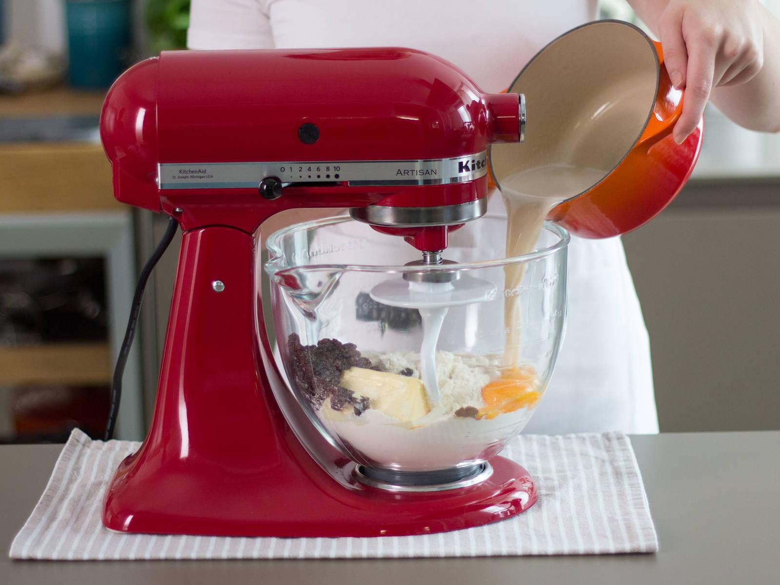 在立式搅拌机中加入部分面粉、第一步中制好的黄油、葡萄干、蛋黄、肉桂和牛奶混合物,搅拌3-5分钟。盖住面团,让其在温暖环境中静置30-35分钟。
