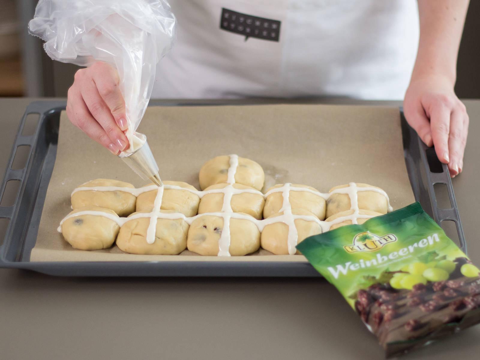 将糖衣挤到面团上,做出十字状。将面团放到预热好的烤箱中,以200度烘焙20-25分钟,至面团外表呈金黄色。可以抹上黄油和果酱享用!