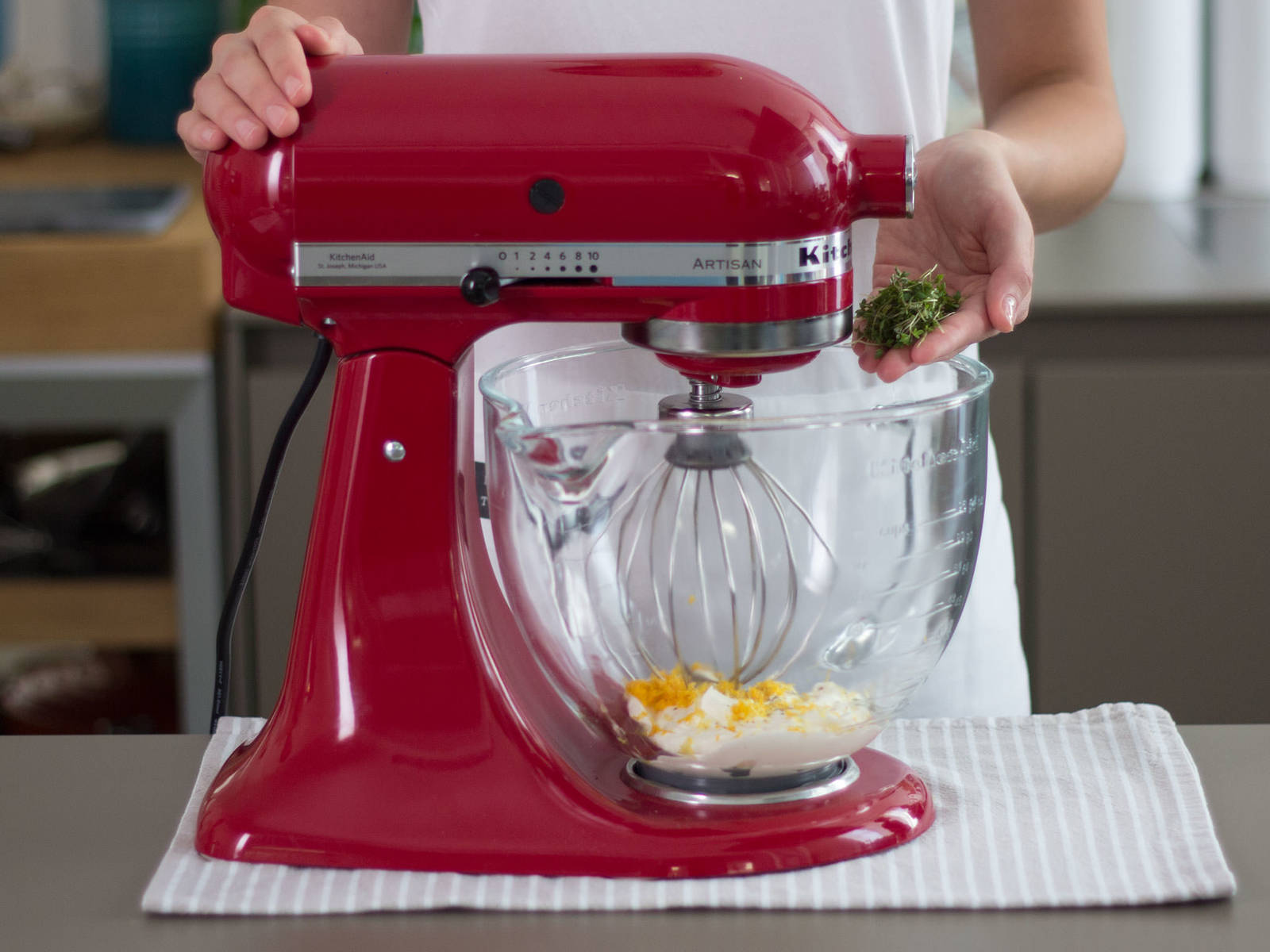 向干净的立式搅拌机碗中放入鲜奶油、糖、柠檬与橙子皮碎、独行菜,搅拌2-3分钟,至鲜奶油起泡,食材混合均匀。加盐与胡椒粉调味。