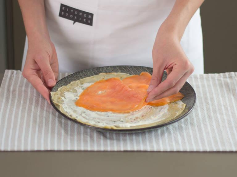 Sobald die Crêpes abgekühlt sind, mit einer dünnen, gleichmäßigen Schicht Crème fraiche versehen und mit Räucherlachs belegen. Zusammengerollt mit einem Klacks Crème fraiche und Lachsrogen servieren. Guten Appetit!
