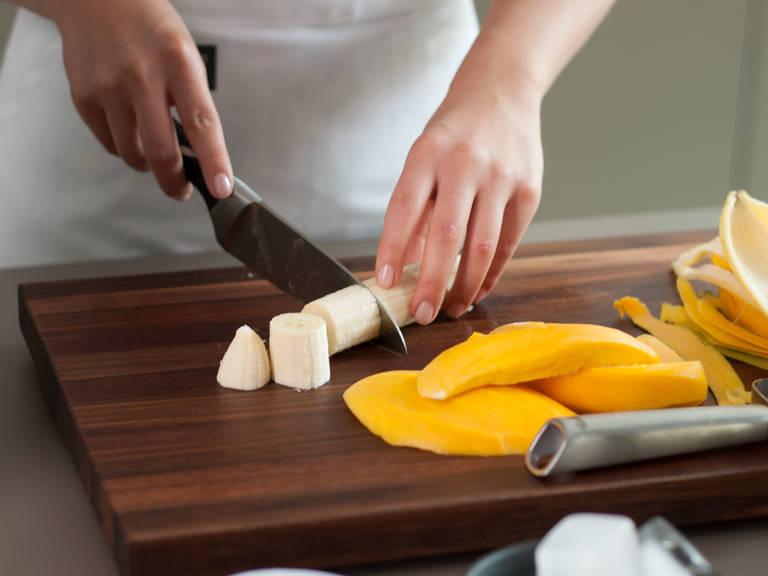 Banane schälen und in grobe Stücke schneiden. Mango schälen und Fruchtfleisch vom Kern schneiden.