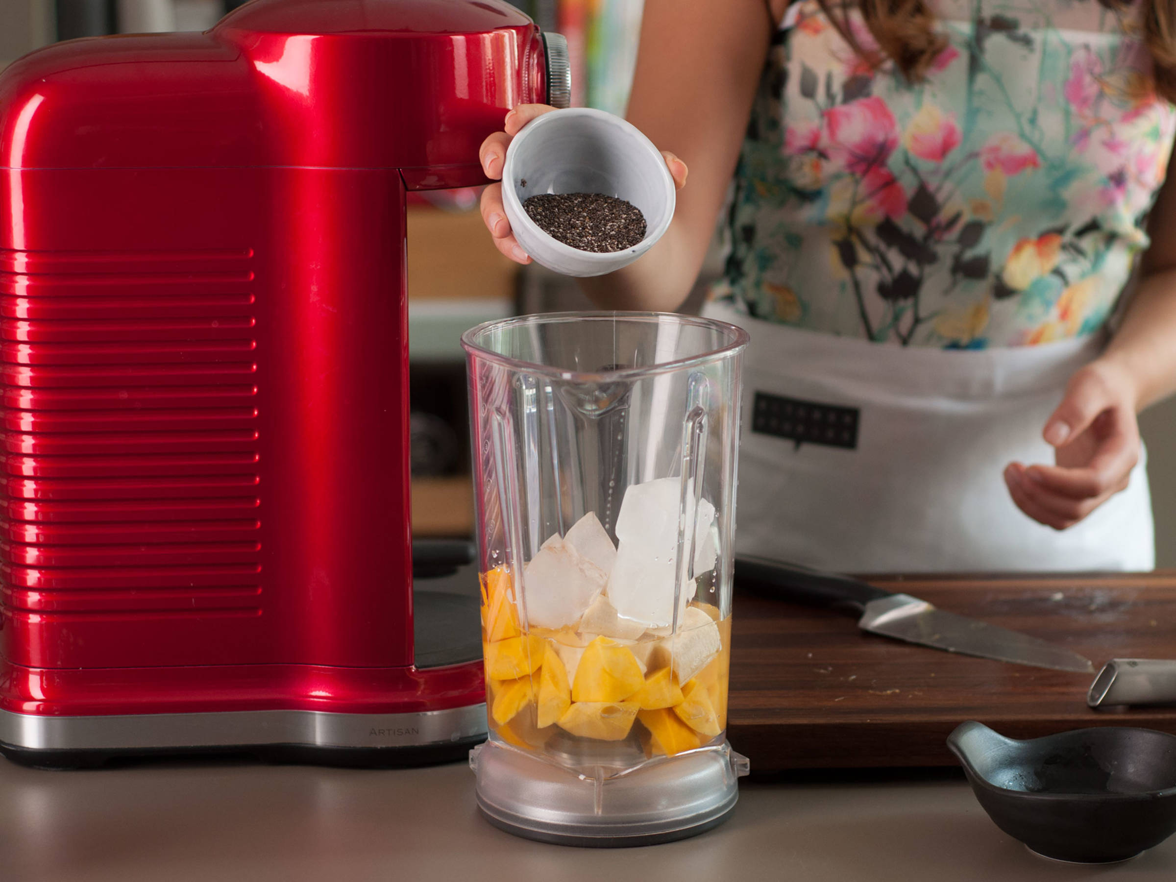 Add mango, banana, ice cubes, water, and chia seeds to blender.