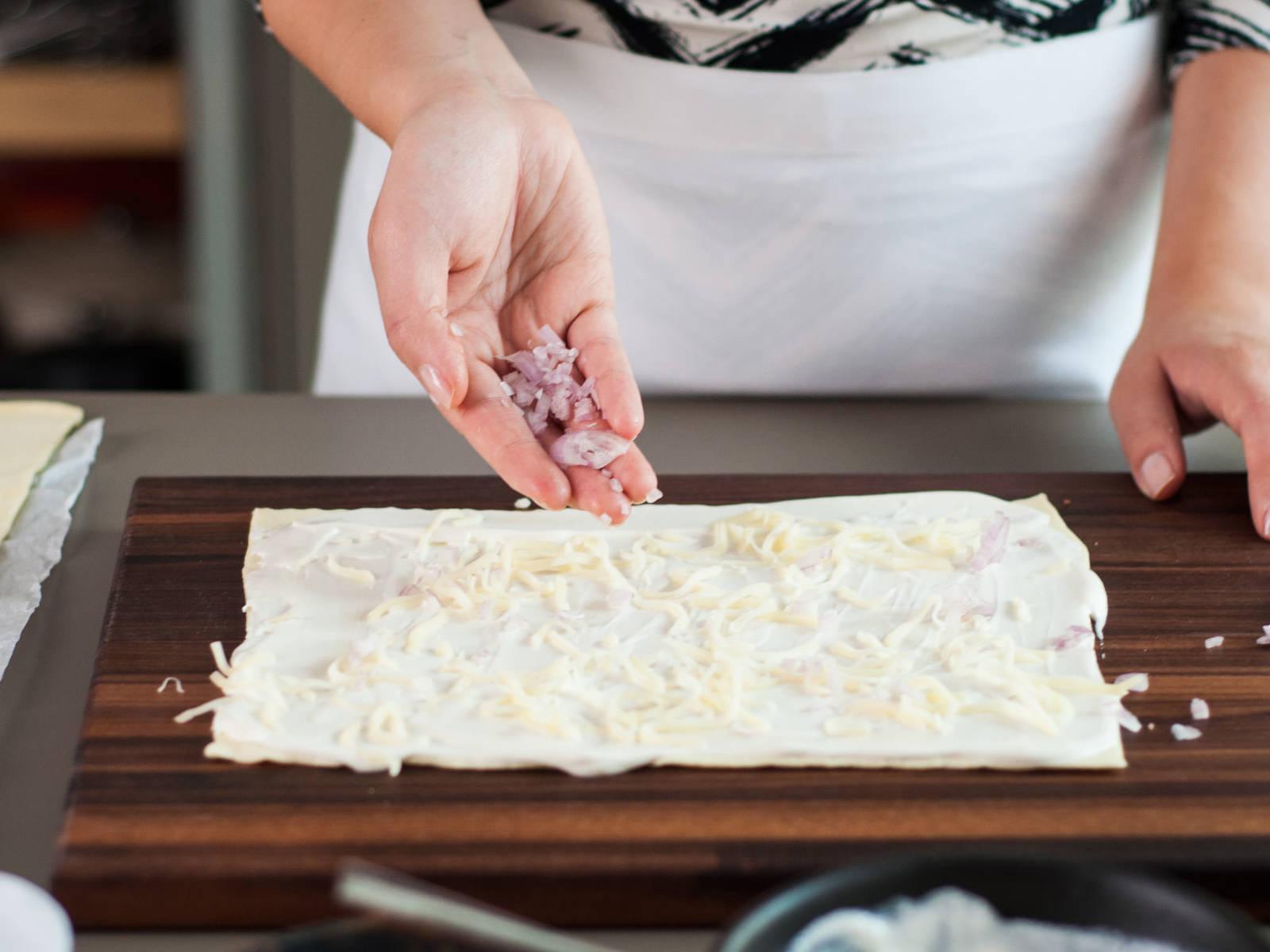 Blätterteig halbieren. Die eine Hälfte mit saurer Sahne bestreichen und mit Käse und Schalotten bestreuen. Mit Salz und Pfeffer würzen.