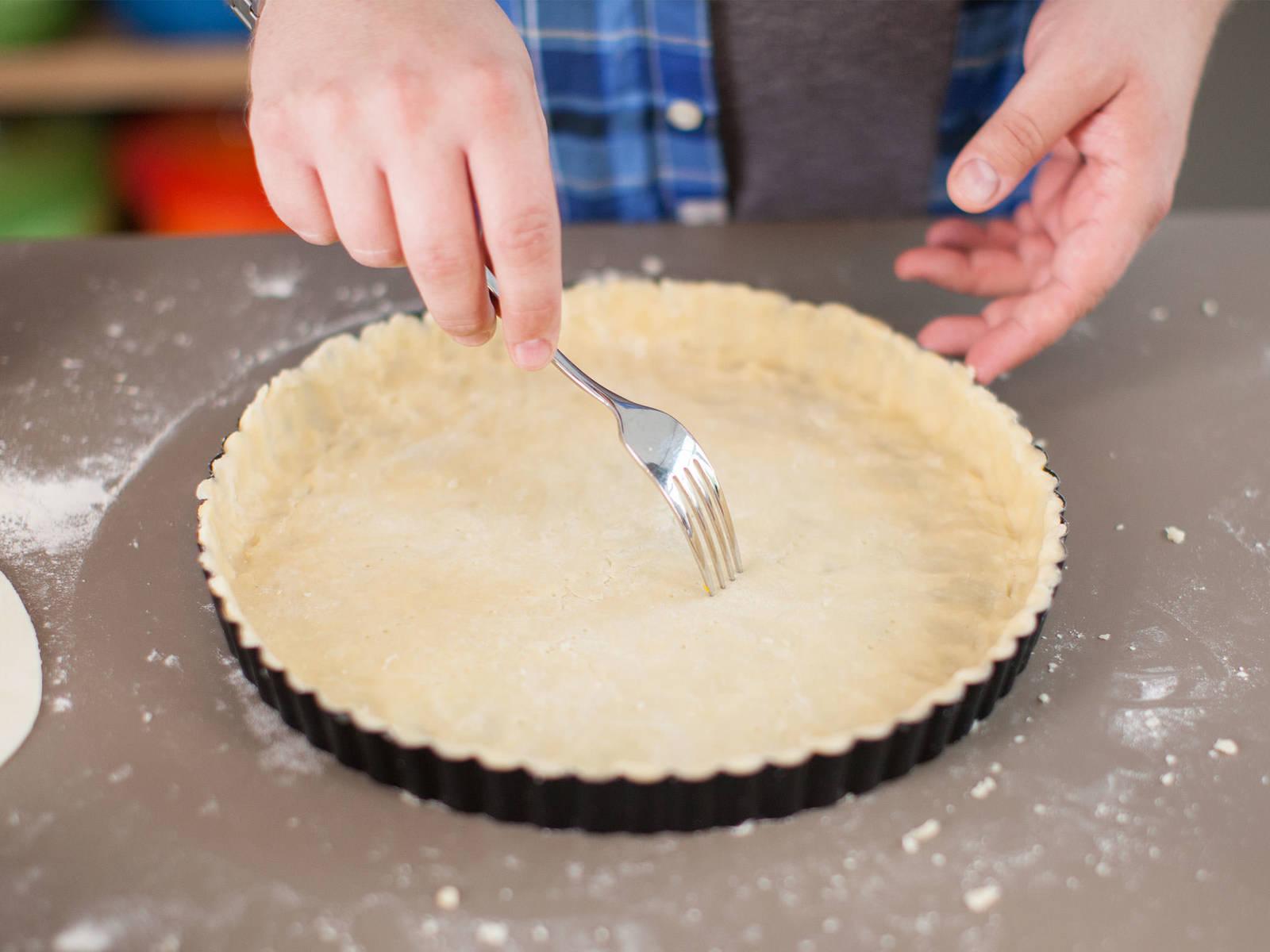 在台面撒少许面粉。从冰箱取出面团,并擀成薄片。在馅饼盘上刷油,然后放入面团。必要时可剪掉边缘。放入一个底部有孔的派盘,放回冰箱,静置 10 分钟。