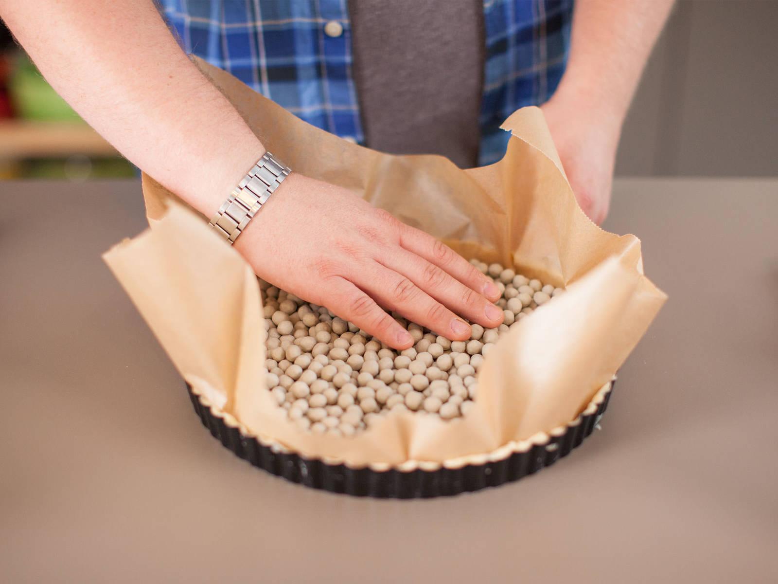 Ein Stück Backpapier vorsichtig auf den ausgelegten Teig geben, mit Keramik-Backbohnen füllen und im vorgeheizten Backofen ca. 15 – 20 Min. blind backen, bis die Ränder goldbraun sind.