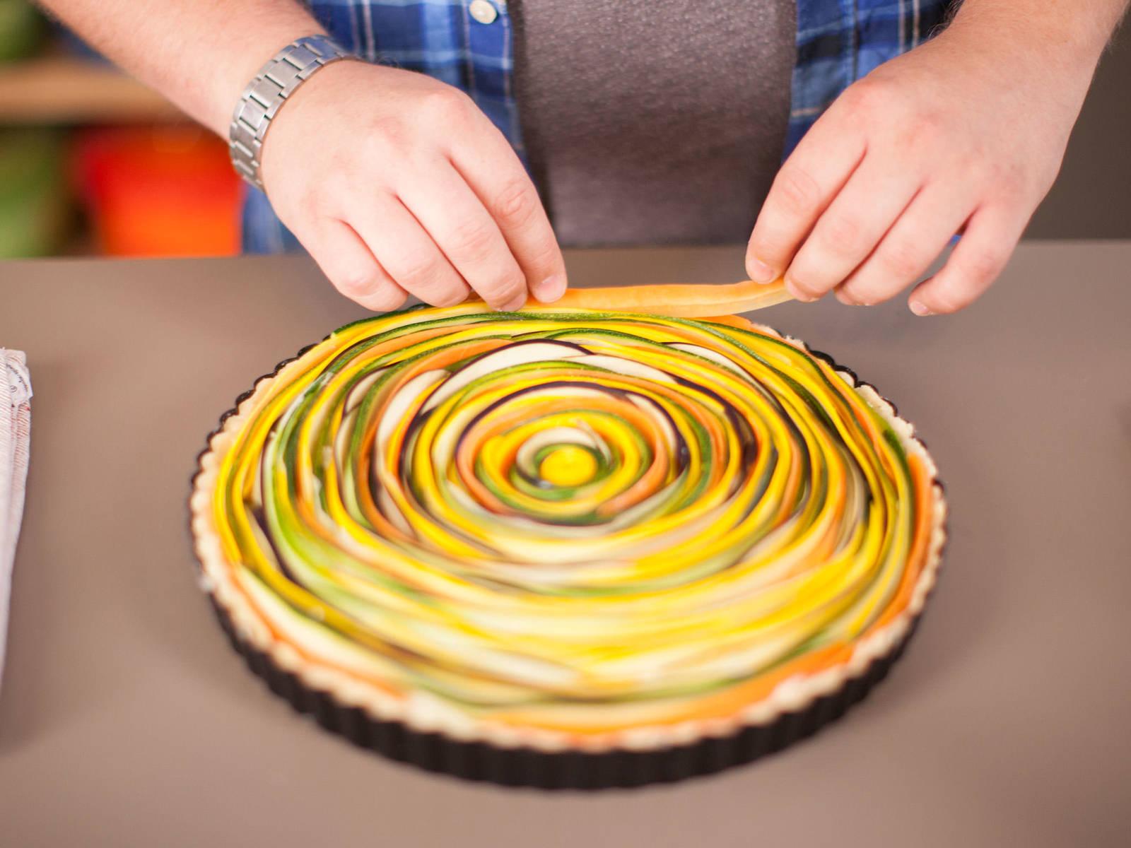 Die Temperatur des Backofens auf 190°C erhöhen. Backpapier und Backerbsen entfernen. Käsemasse in die Tarte geben. Vorsichtig Gemüsespirale darauf legen und lose Streifen in die Ränder stecken. Tarte mit Olivenöl einpinseln und ca. 40 – 50 Min. backen.