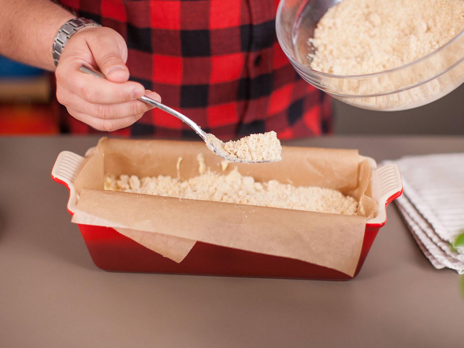 向面包盘中铺上烘焙纸。将面糊倒入面包盘中,并撒上酥粒。放入预热至160摄氏度的烤箱中,烘烤40-45分钟。