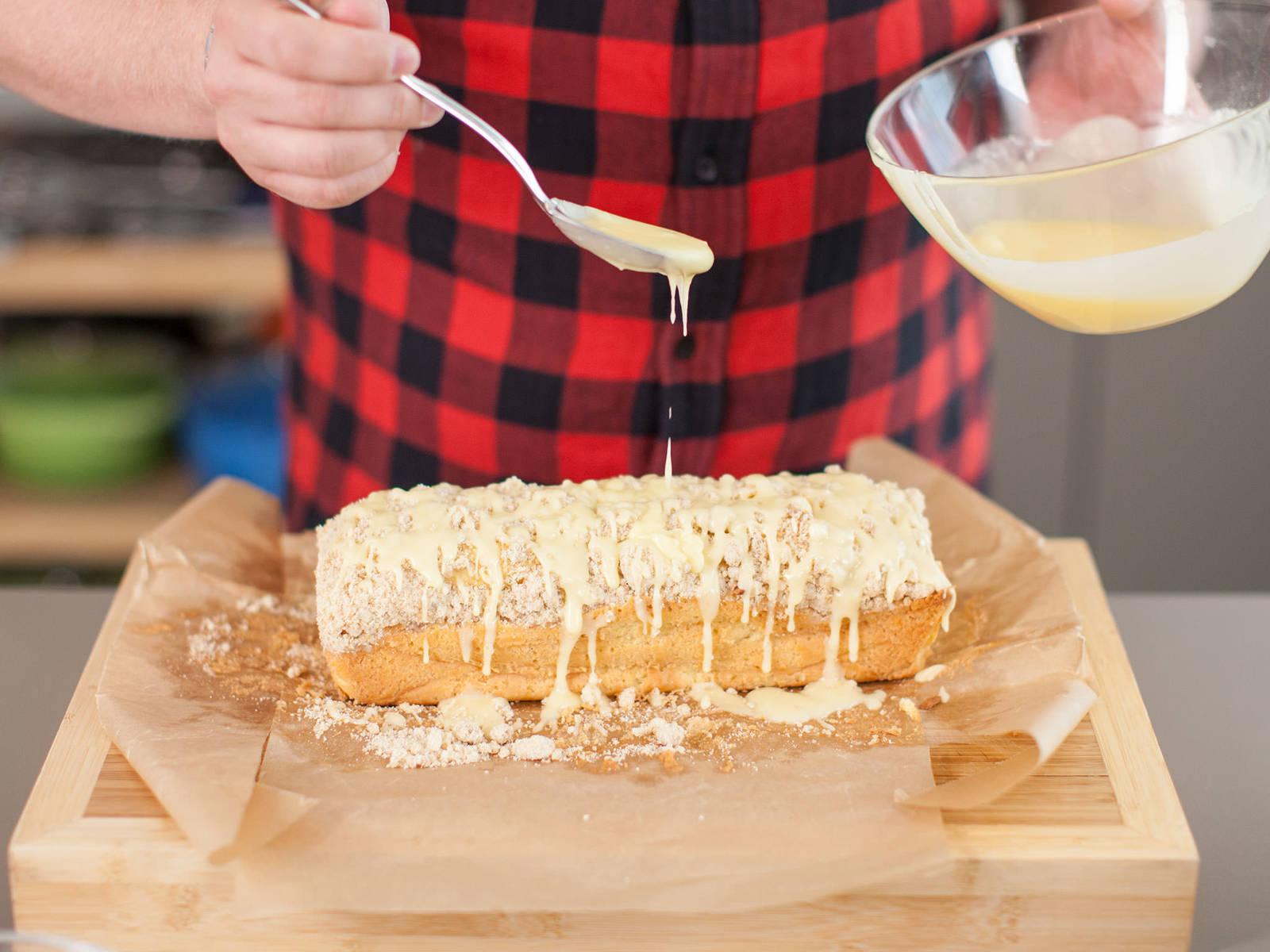 从烤箱中取出蛋糕,放到冷却架上,静置冷却。同时,融化剩余的黄油,将其与剩余的蛋酒、朗姆酒和糖粉混合,将混合物涂到蛋糕表面。