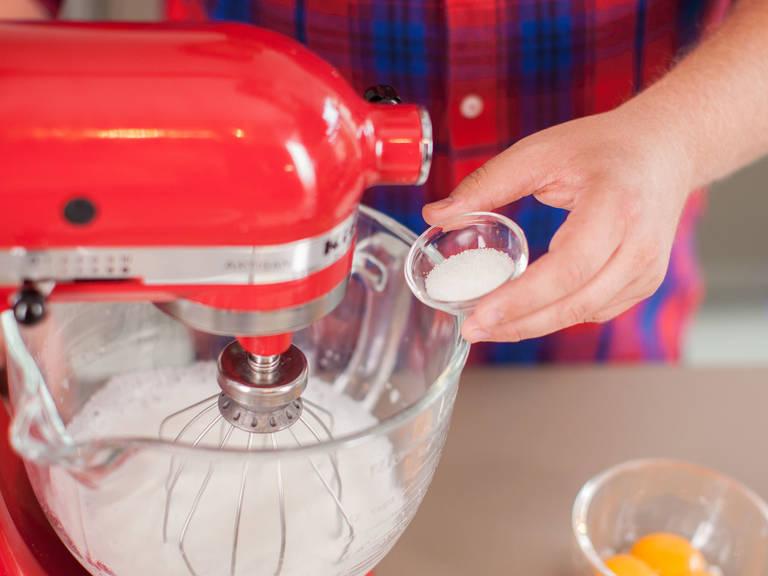 Eier trennen und Eigelbe beiseitestellen. Eiweiß in eine Küchenmaschine geben und schaumig schlagen. Einen Teil des Zuckers hinzugeben und steif schlagen. Eischnee in eine große Schüssel geben.