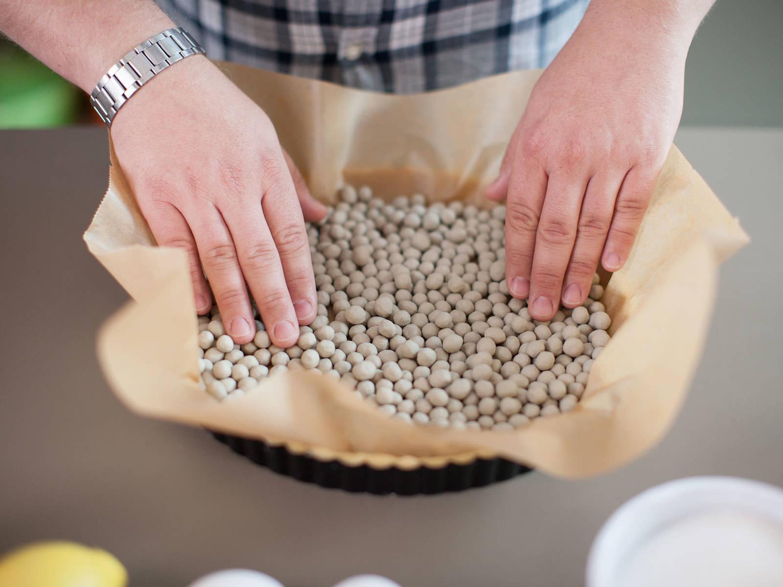预热烤箱至200摄氏度。将烘焙纸铺在派皮上,用派珠或豆子压在上面,烘烤20-25分钟。从烤箱中取出后,去掉派珠,静置冷却。将烤箱调至180摄氏度。