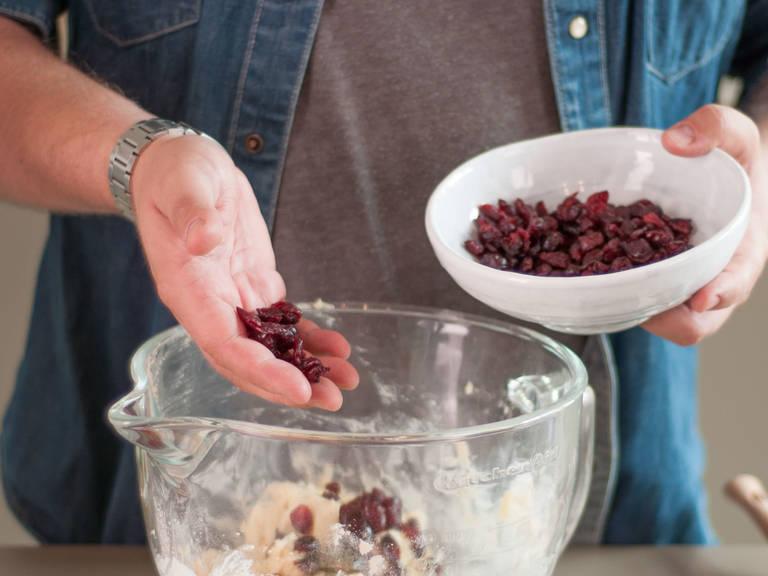 向面团中加入蔓越莓,并搅拌均匀。