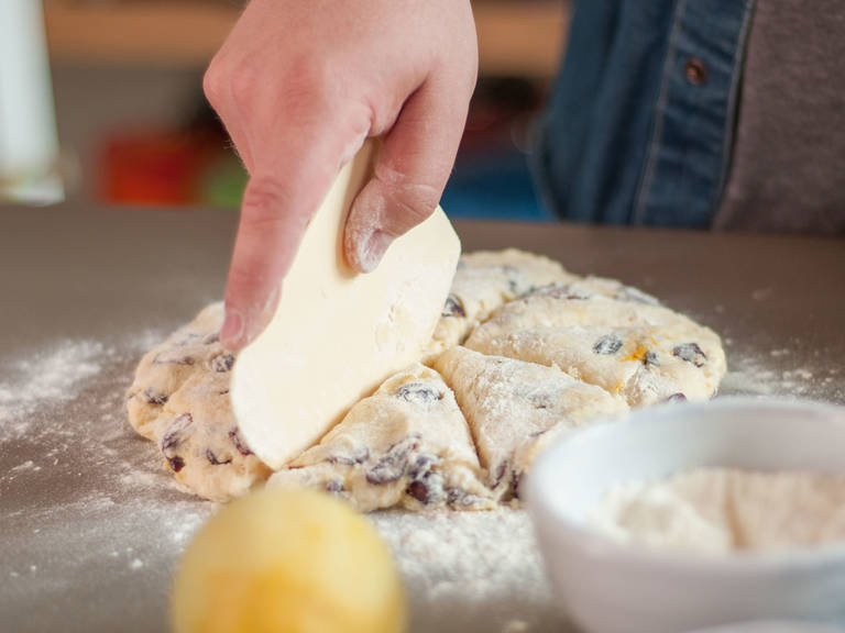 Transfer dough to floured work surface, spread out two fingers thick, and cut into triangular slices. Place each scone on a lined baking sheet and bake in preheated oven at 200°C/400°F for approx. 18 – 20 min. or until they are golden brown.