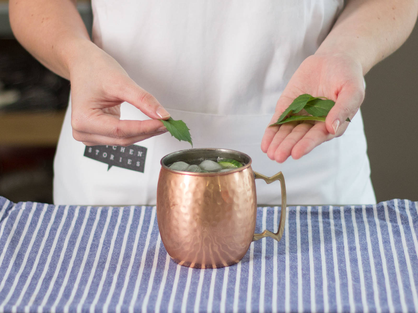 Add cucumbers to mug and garnish with mint leaves.