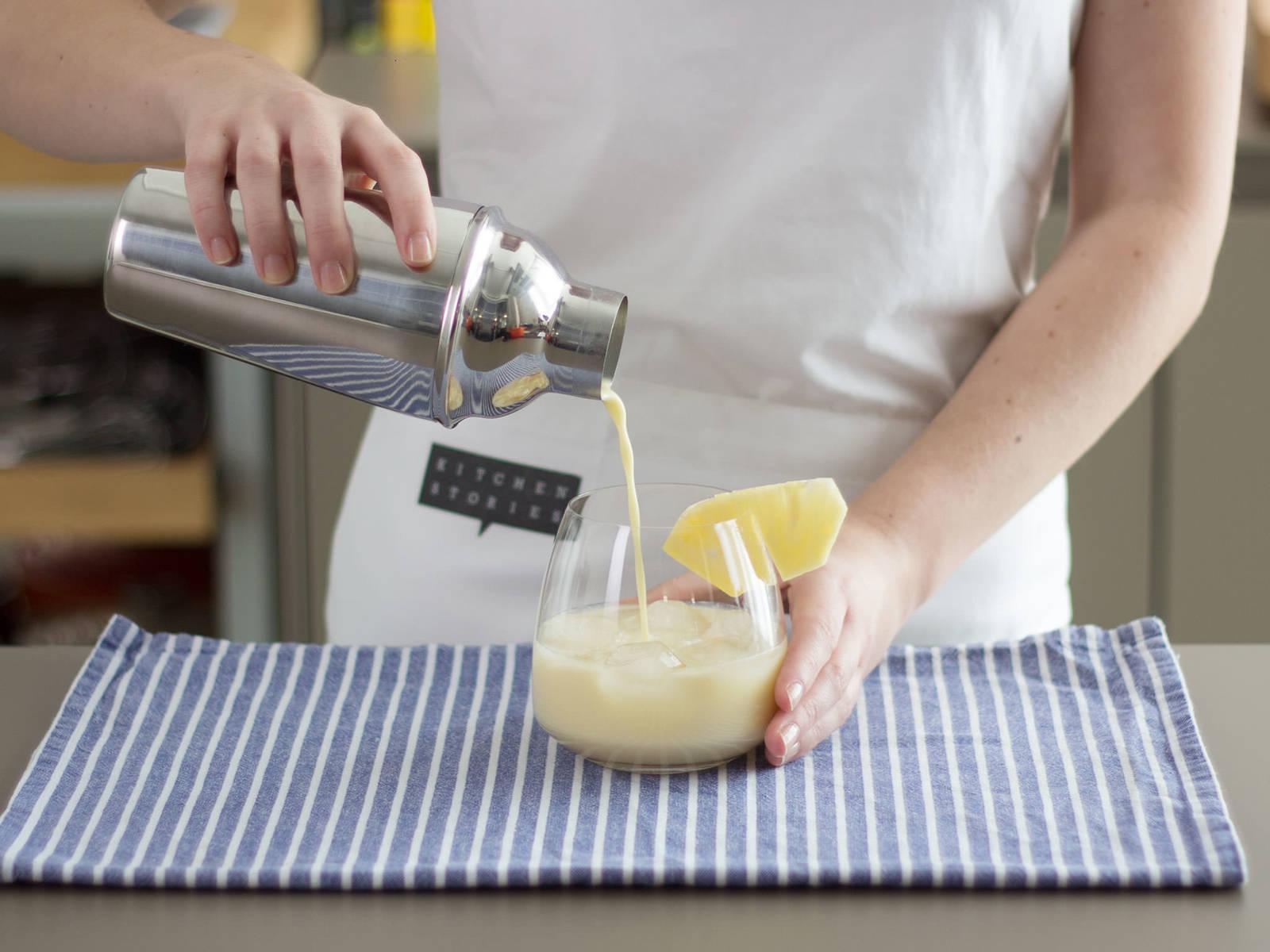 Die Mischung direkt ins Glas mit Eiswürfeln passieren und mit Ananasscheibe garnieren. Prost!