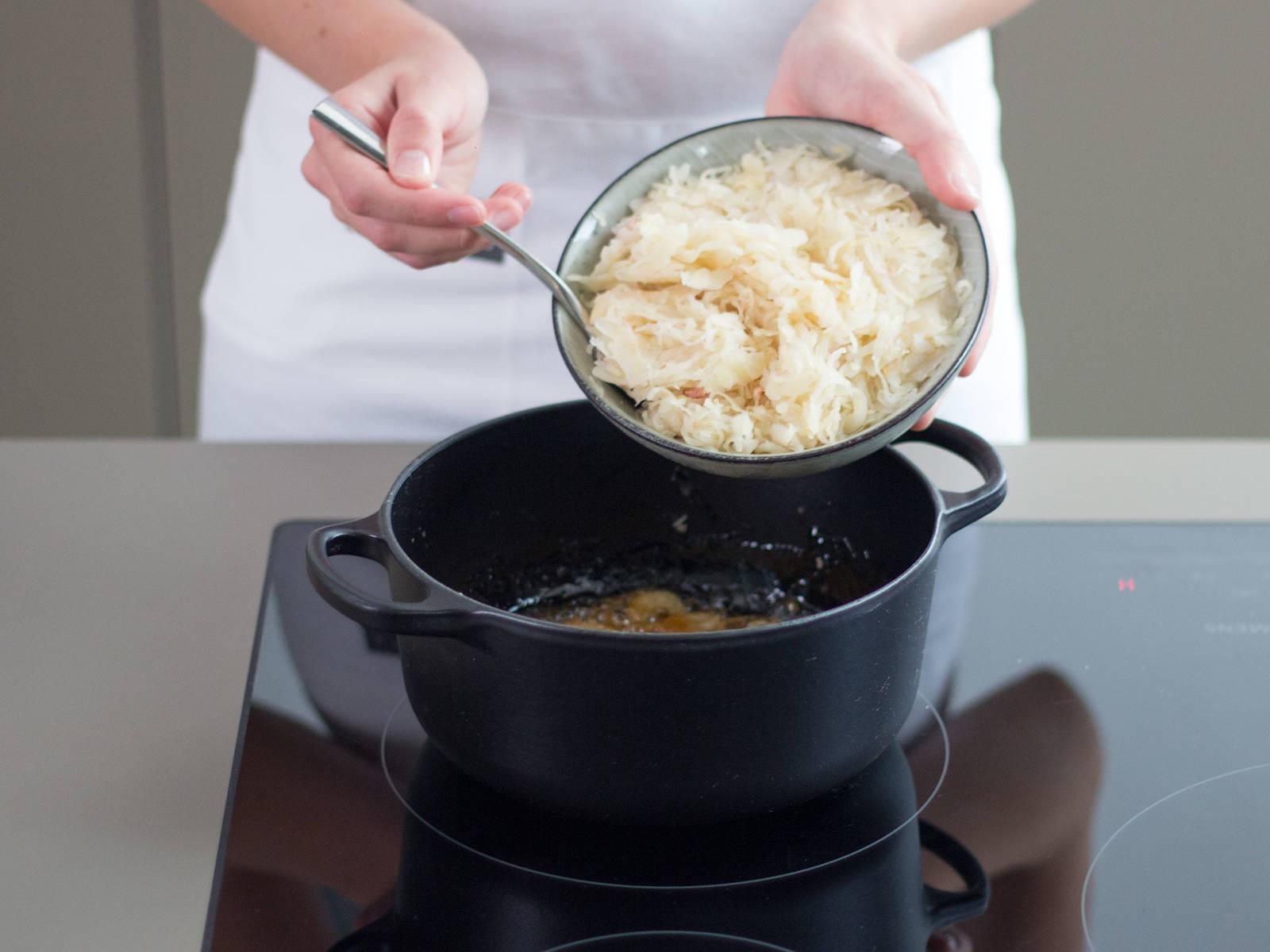 Zucker in einem großen Topf karamellisieren lassen. Zwiebelringe hinzufügen und unter häufigem Rühren braun werden lassen. Sauerkraut hinzufügen und gut vermengen.