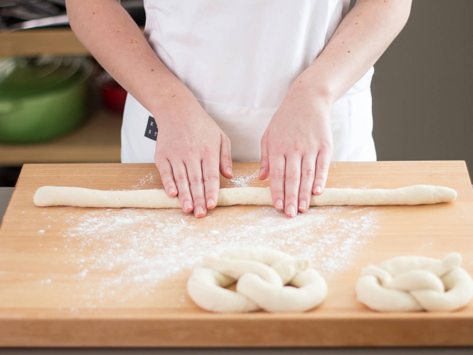 将烤箱预热至200摄氏度。向工作台上撒少许面粉,然后再次揉面团,并将面团均分成10份。将每个小面团揉成中间稍厚的长条状,再盘成扭结饼状。