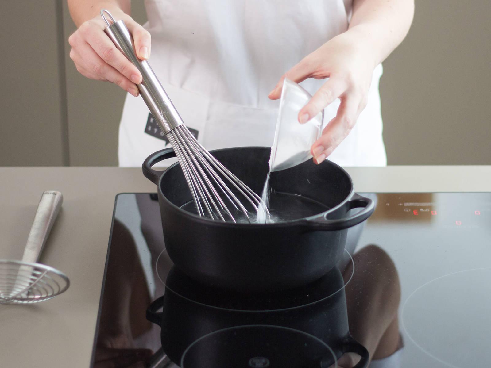 将水加入大锅中,煮至沸腾后加入剩余的盐。调至低温,并缓慢加入小苏打。注意水温不宜过高,以免泡沫迅速溢出。