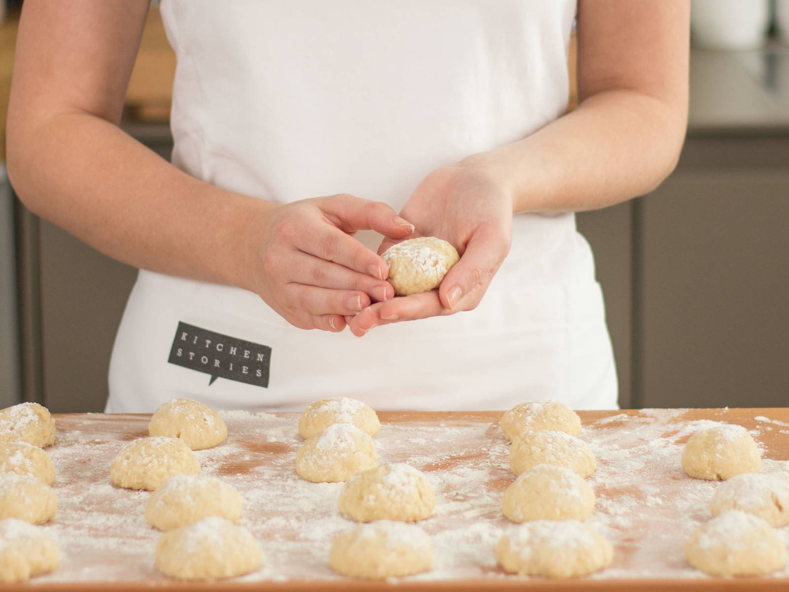 Transfer dough to a floured work surface. Now, form the dough into small, golf ball-sized rounds. Allow to rise for approx. 25 – 30 min. Then, flatten out dough and with a small cookie cutter, cut out the center of the dough. Allow dough to rise for approx. another 50 – 60 min.