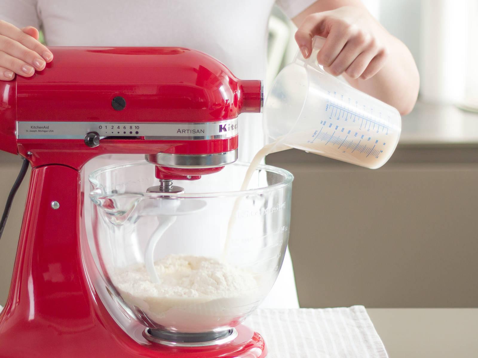 预热烤箱至180摄氏度/350华氏度。 在量杯中以温水溶解酵母和糖,然后将溶解后的混合物与面粉、盐和植物油一同倒入立式搅拌机中。搅拌至面团呈现柔软均匀的状态。将面团盖住,让其在温暖的室温中发酵约60分钟。