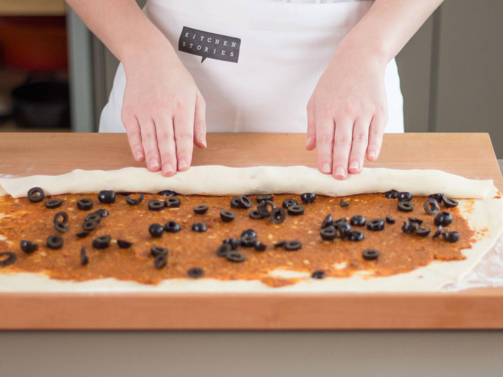 在工作台面上撒上些许面粉,将面团摊平后,用擀面杖擀成较大的长方形。将西红柿糊均匀地抹到面团上,并撒上一些橄榄碎。卷起面团,使其呈一个长条状。