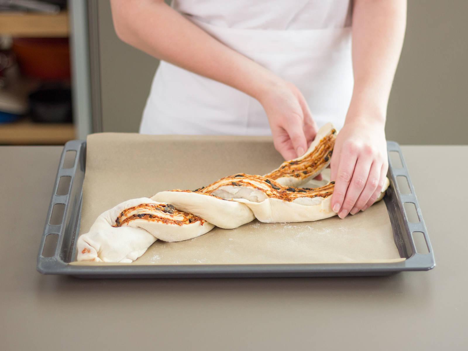 将面团放到铺好烘焙纸的烤板上。面团切半,然后编成辫子状。 将加工好的面团转移到预热好的烤箱中,以180摄氏度/350华氏度的温度烘焙35-45分钟。