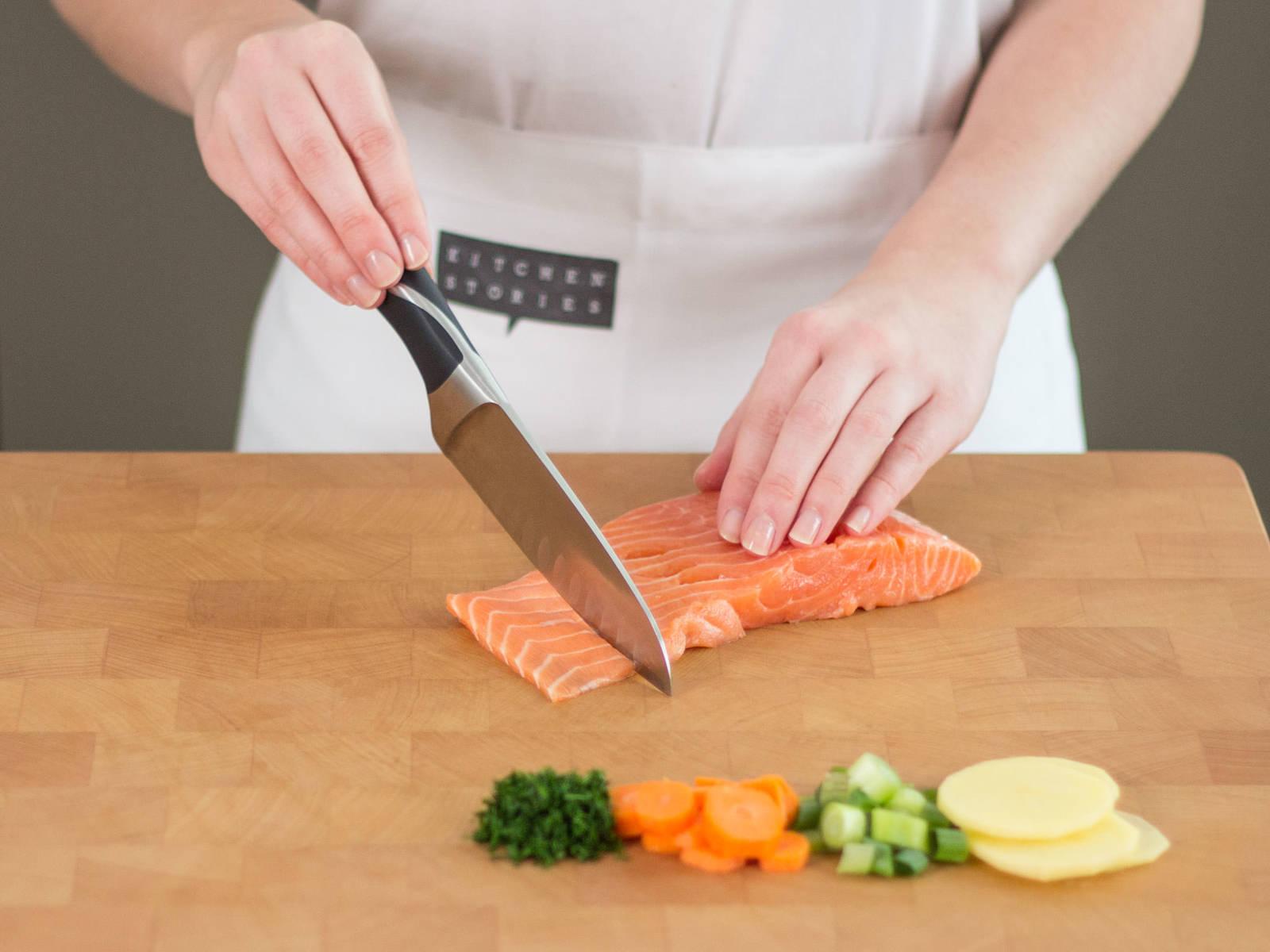 Backofen auf 200°C vorheizen. Kartoffeln schälen und in dünne Scheiden schneiden. Frühlingszwiebel diagonal in Ringe schneiden. Dill und Petersilie fein hacken. Karotten in mundgerechte Stücke schneiden. Knoblauch fein schneiden. Kabeljau und Lachs von ihrer Haut befreien und in mundgerechte Stücke schneiden. Bringt Wasser in einem großen Topf zum Kochen und kocht Kartoffel- und Karotten-Stücke ca. 5 Minuten lang vor. Gießt danach das Wasser ab.